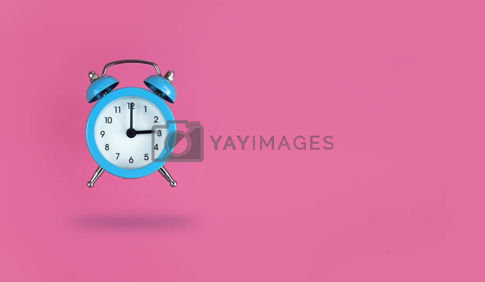 Levitating blue alarm clock on a pink background with copy space.