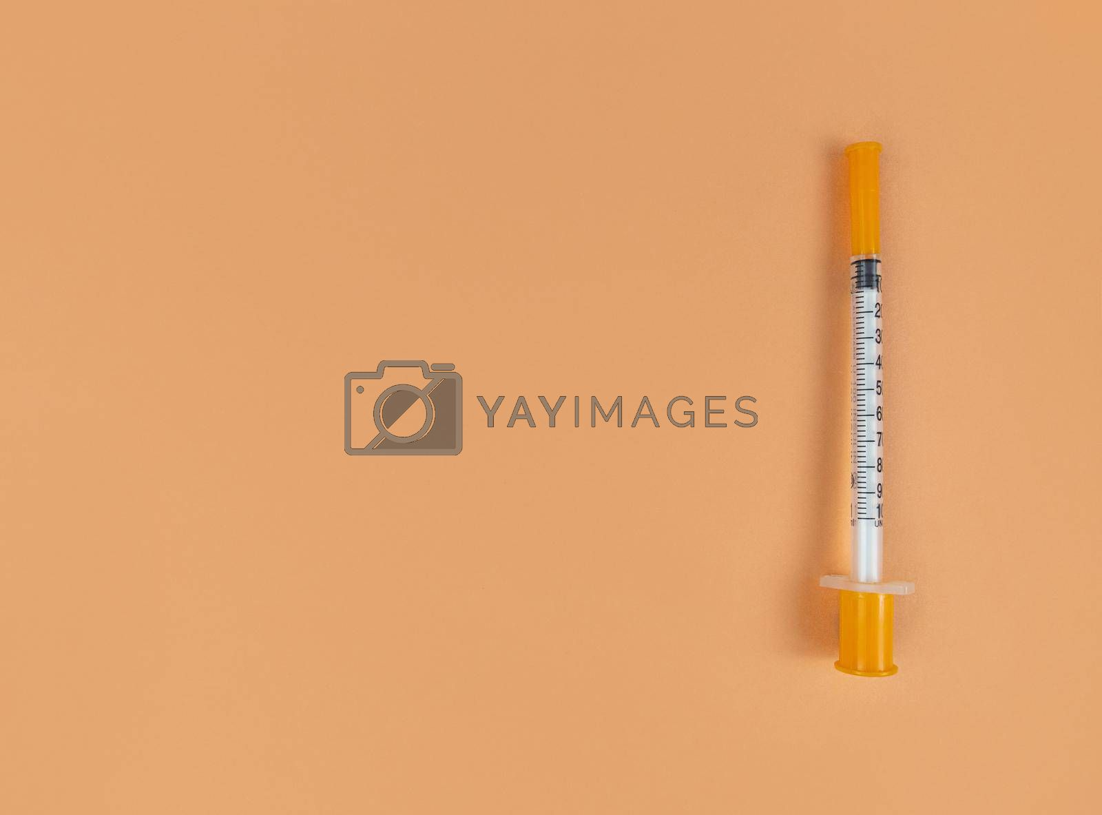 Insulin syringe on an orange background with copy space.