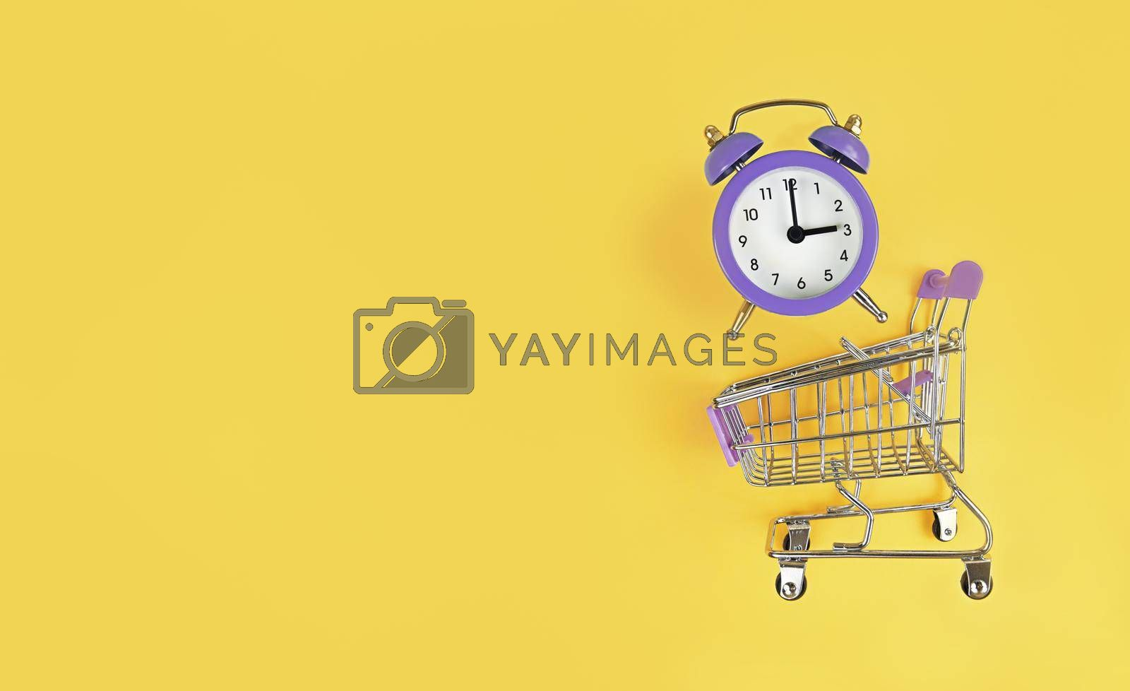 Supermarket trolley and violet alarm clock on a yellow background with copy space. Buy time, busy concept.