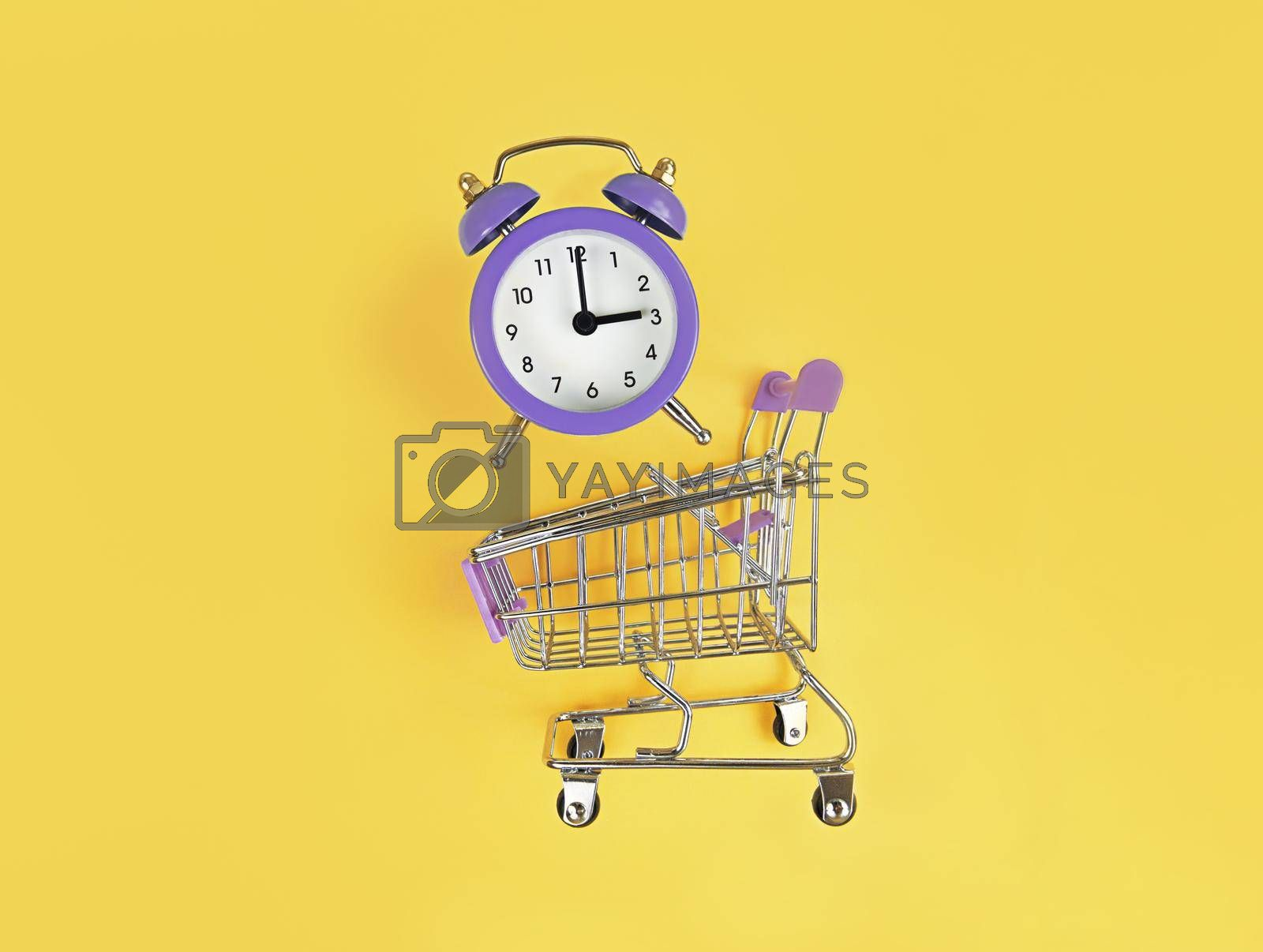 Supermarket trolley and violet alarm clock on a yellow background. Buy time, busy concept.