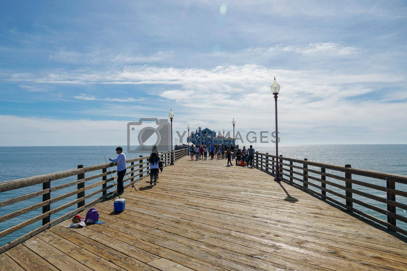 Tourist walking on the Oceanside Pier during blue summer day, Oceanside, northern San Diego County, California. Wooden pier on the western United States coastline. Famous for fisher. March 22nd, 2020