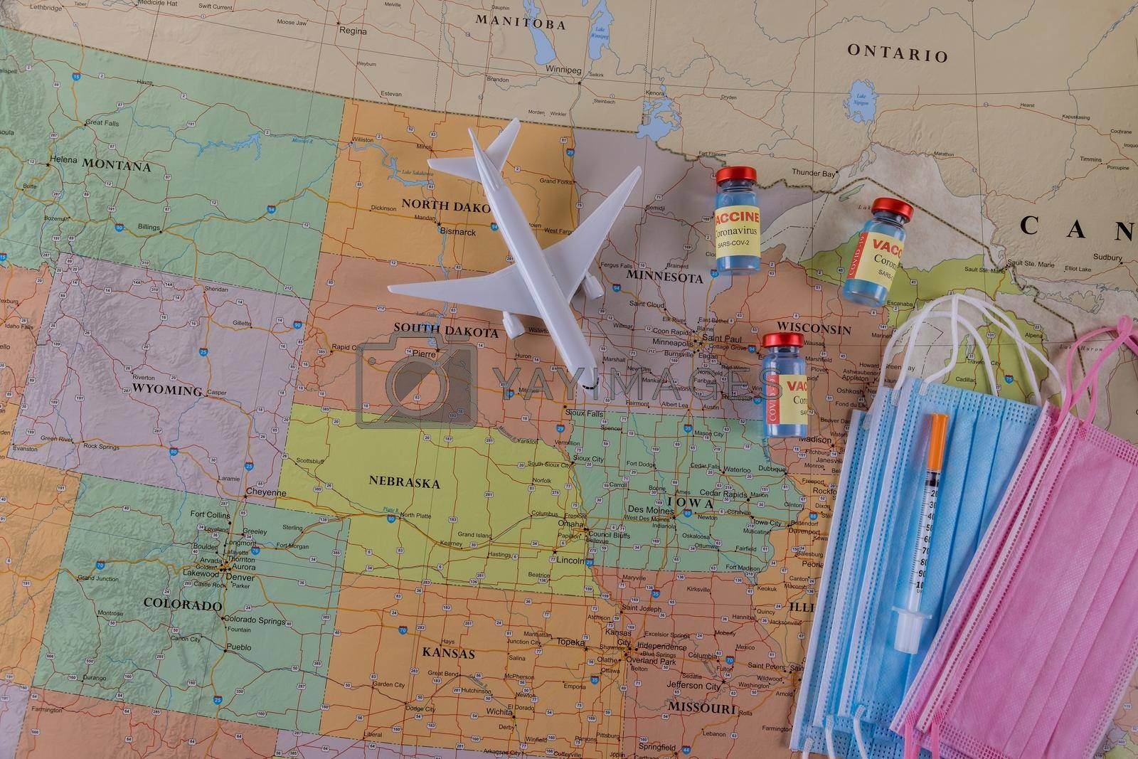 Immunity vaccination for health travelling with surgical mask of defeating Coronavirus Covid-19 vaccine bottles on North America map background