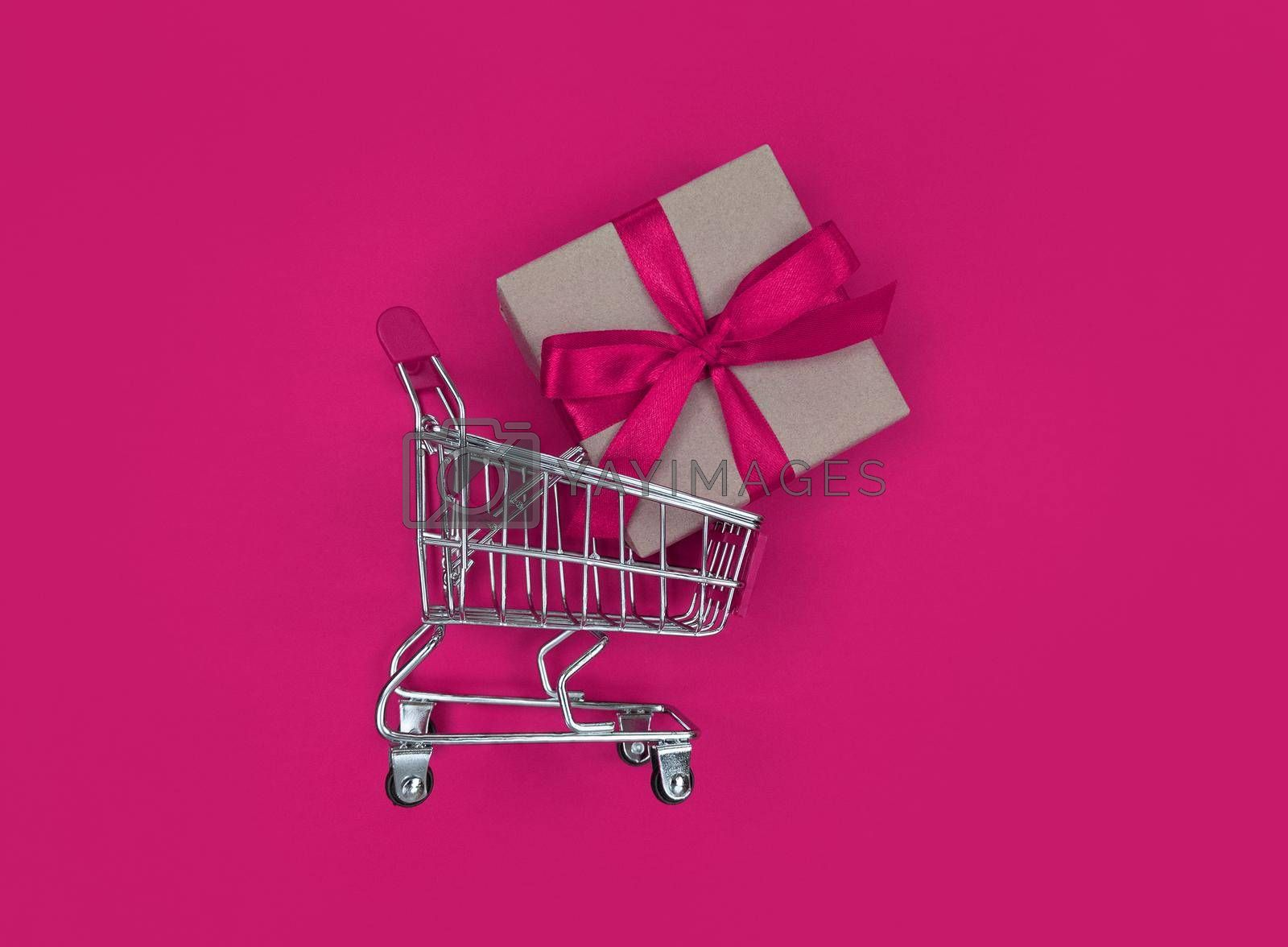 Supermarket trolley and gift box on a pink background. Shopping concept.