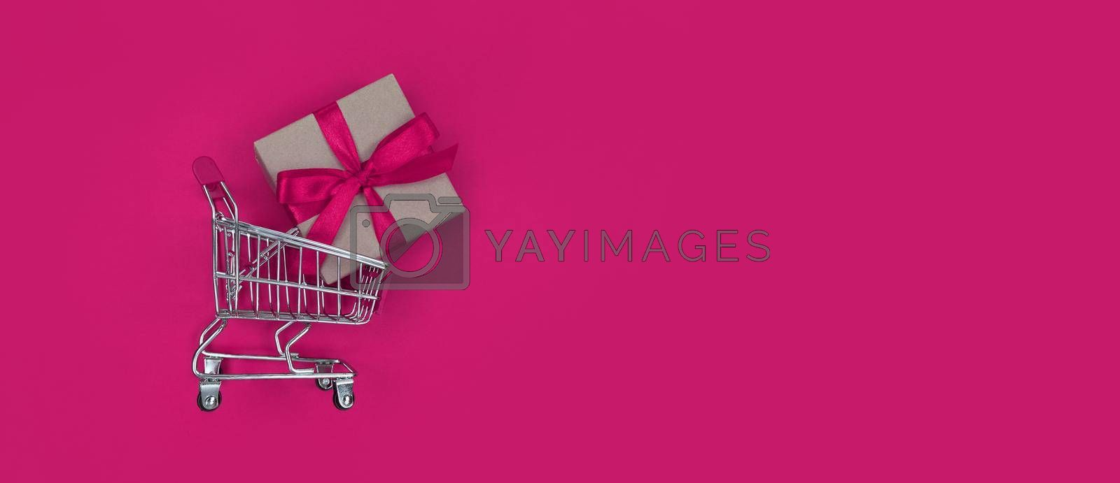 Supermarket trolley and gift box on a pink background with copy space. Shopping concept.