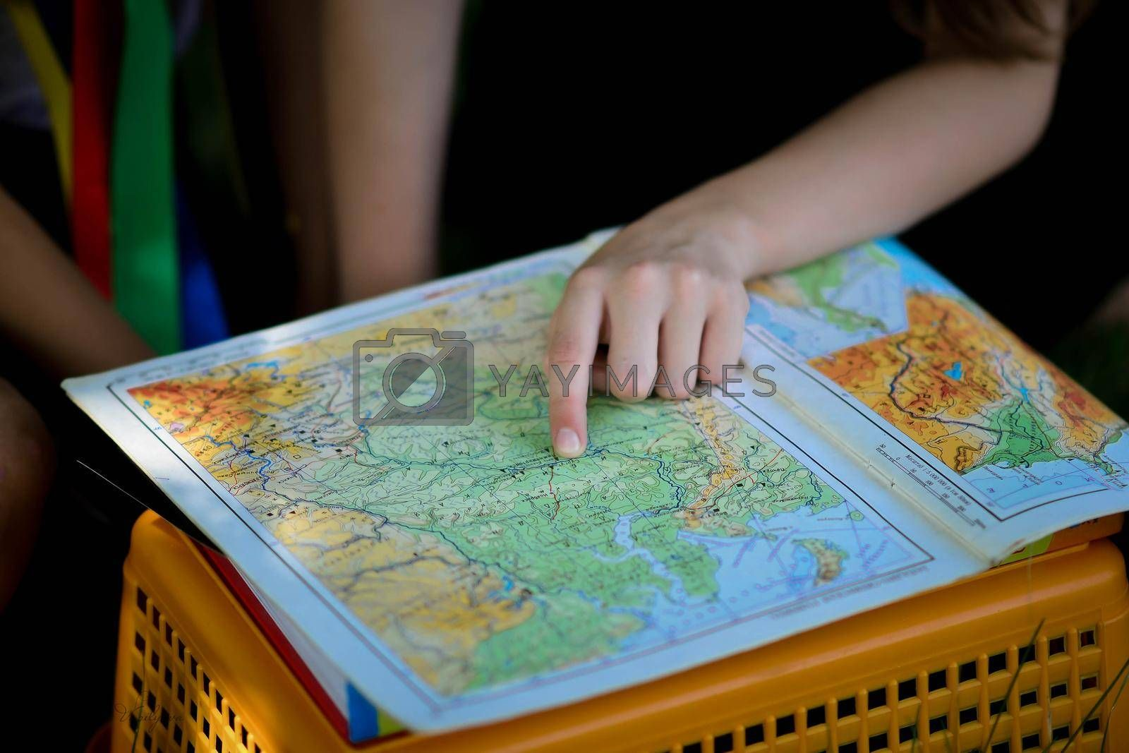 the girl is looking at a geographical atlas. geographical map in the hands of a schoolboy girl. High quality photo