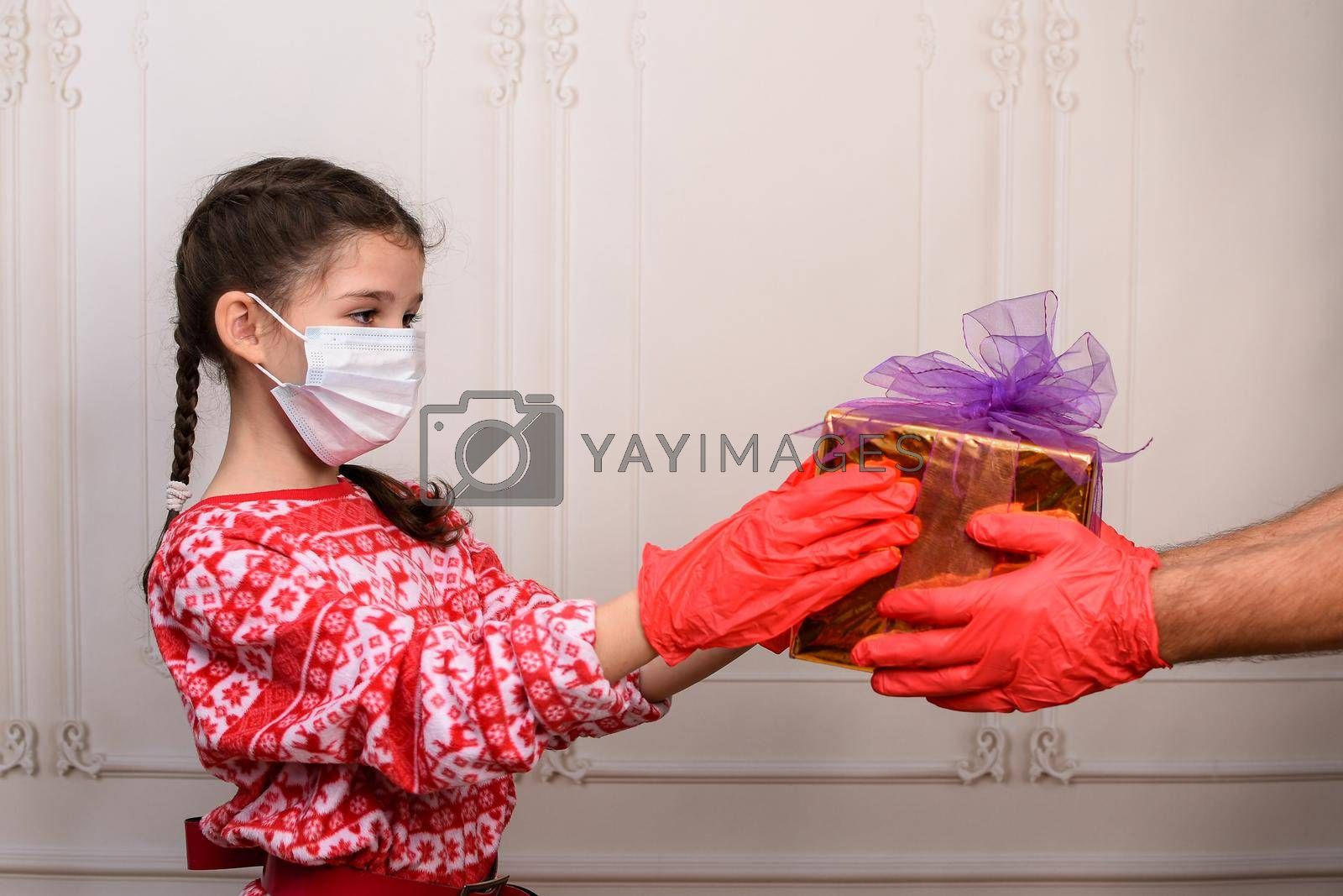 Childhood and people, the concept of Christmas during the epidemic. Girl in a mask and gloves receives a gift. on a light background. studio photo. High quality photo