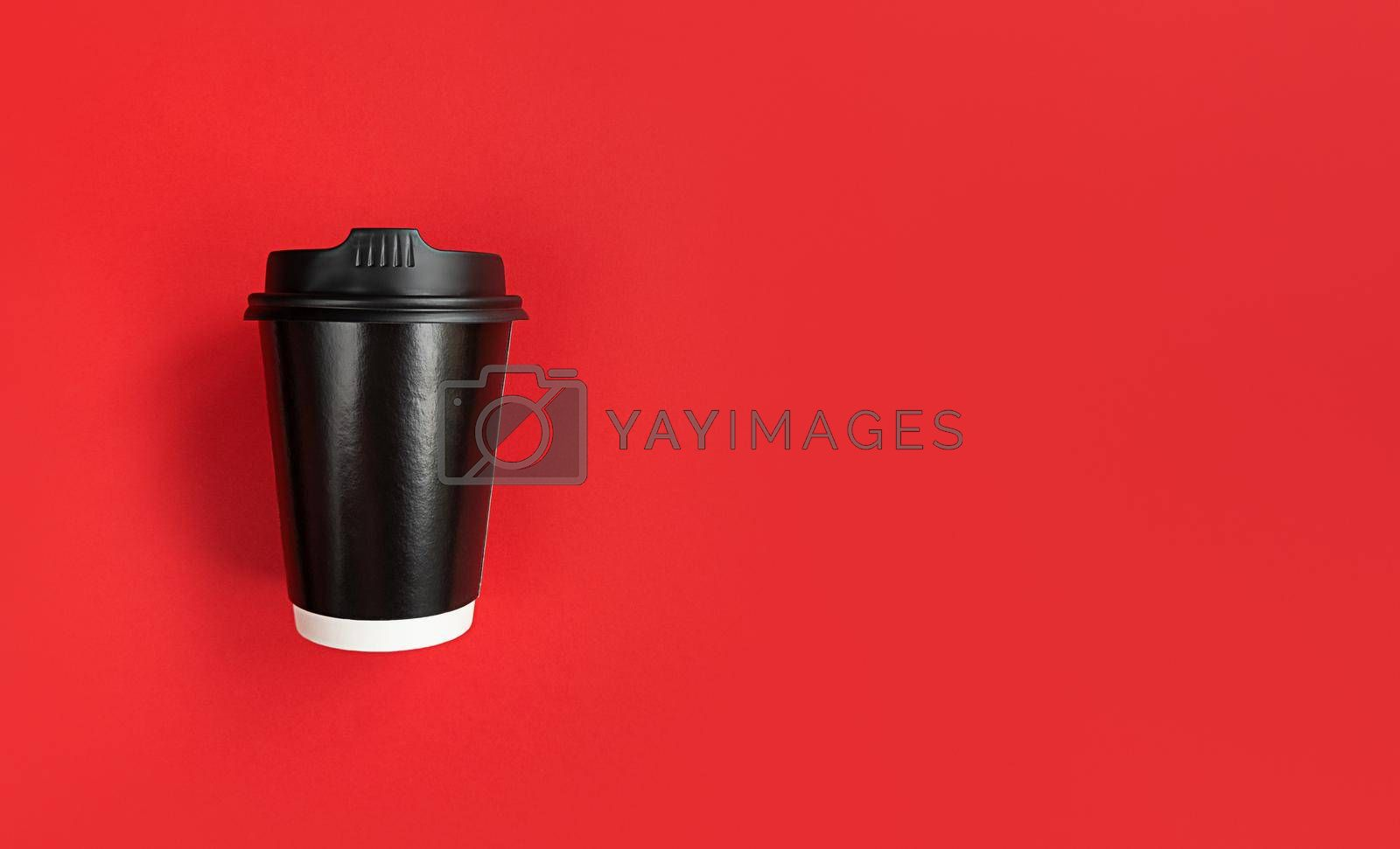 Black paper coffee cup to go on a red background with copy space.