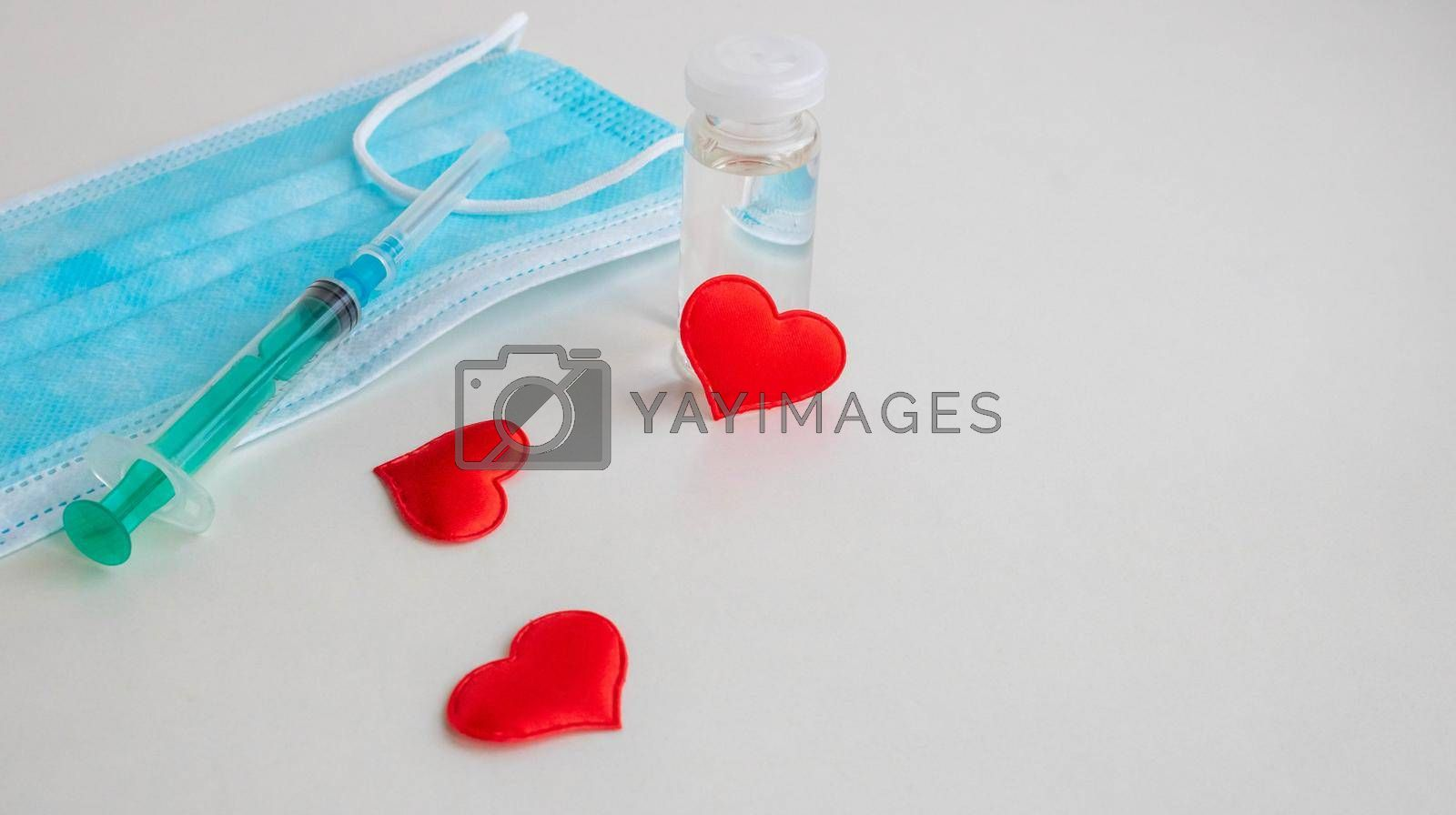 On a white background are a mask, a syringe, a bottle of vaccine and three small red hearts. The concept of medicine and health care.