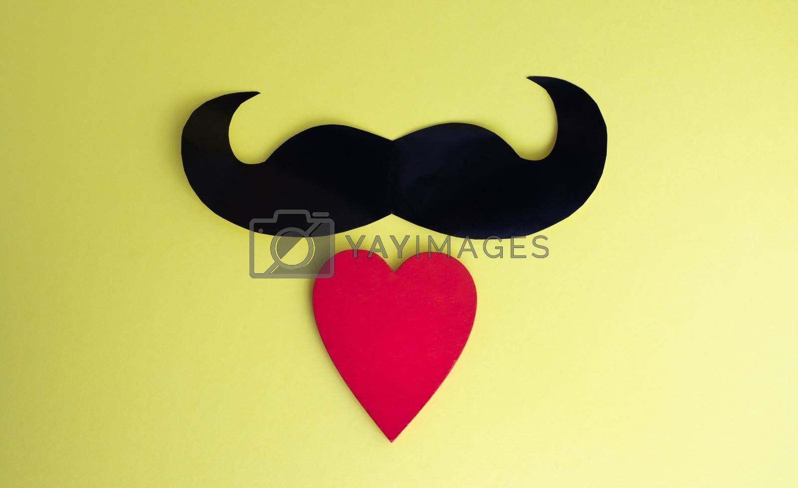 Father's Day concept. Black mustache and red heart on a yellow paper background.