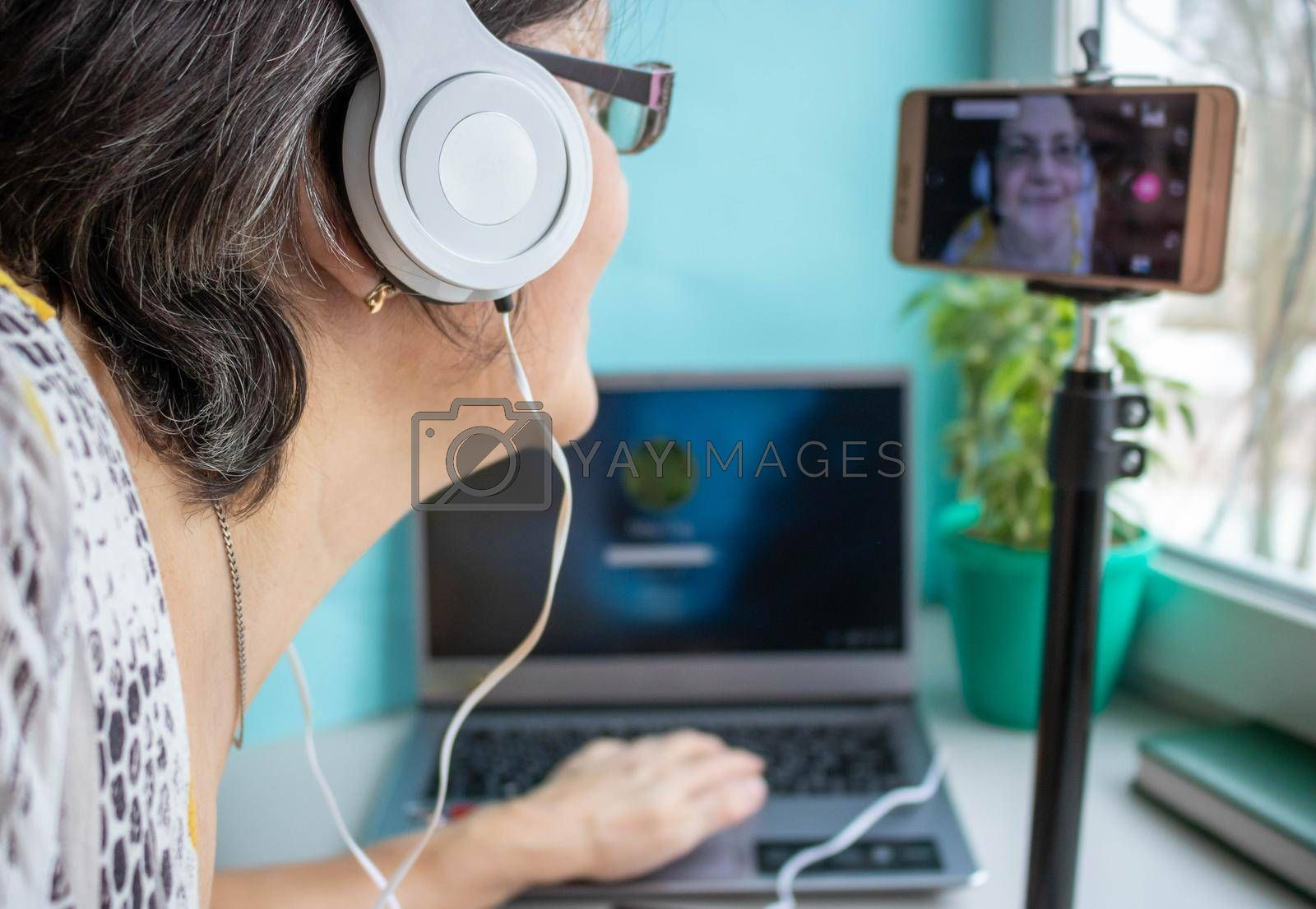 An elderly woman wearing headphones .Work from home online for the elderly.Communication over the Internet.