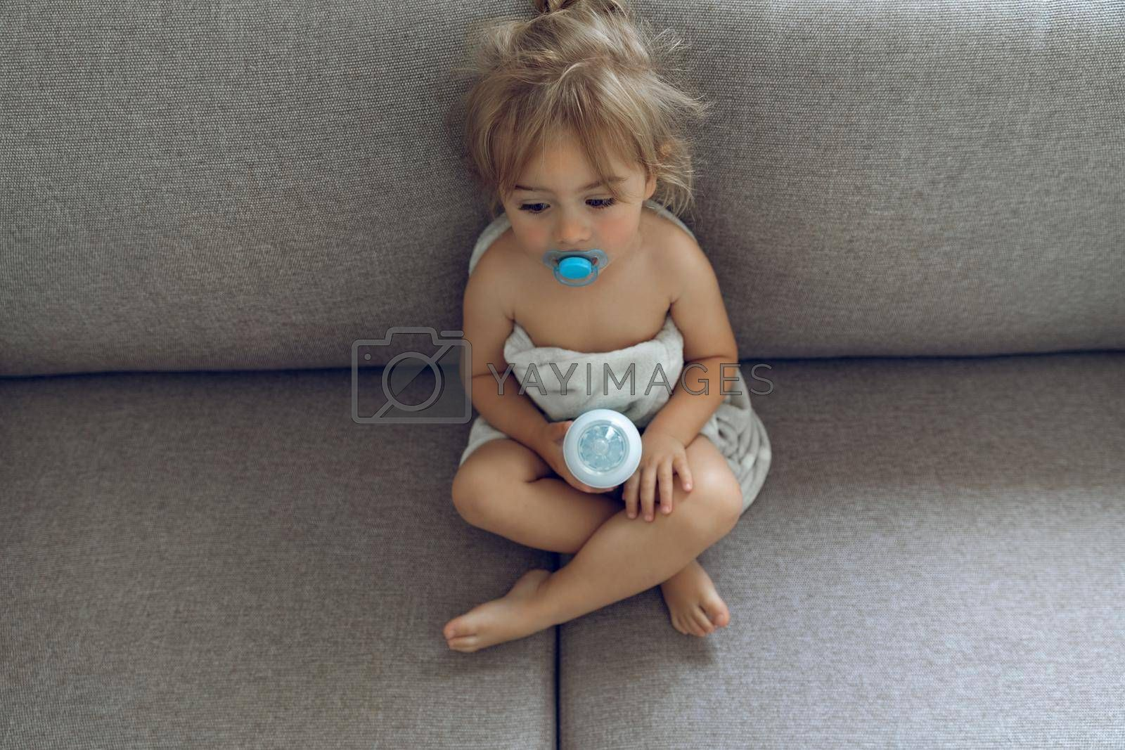 Sweet Adorable Child With Pacifier in the Mouth Sitting on the Sofa at Home Holding Baby Bottle with Milk. Time to Eat. Happy Healthy Childhood.