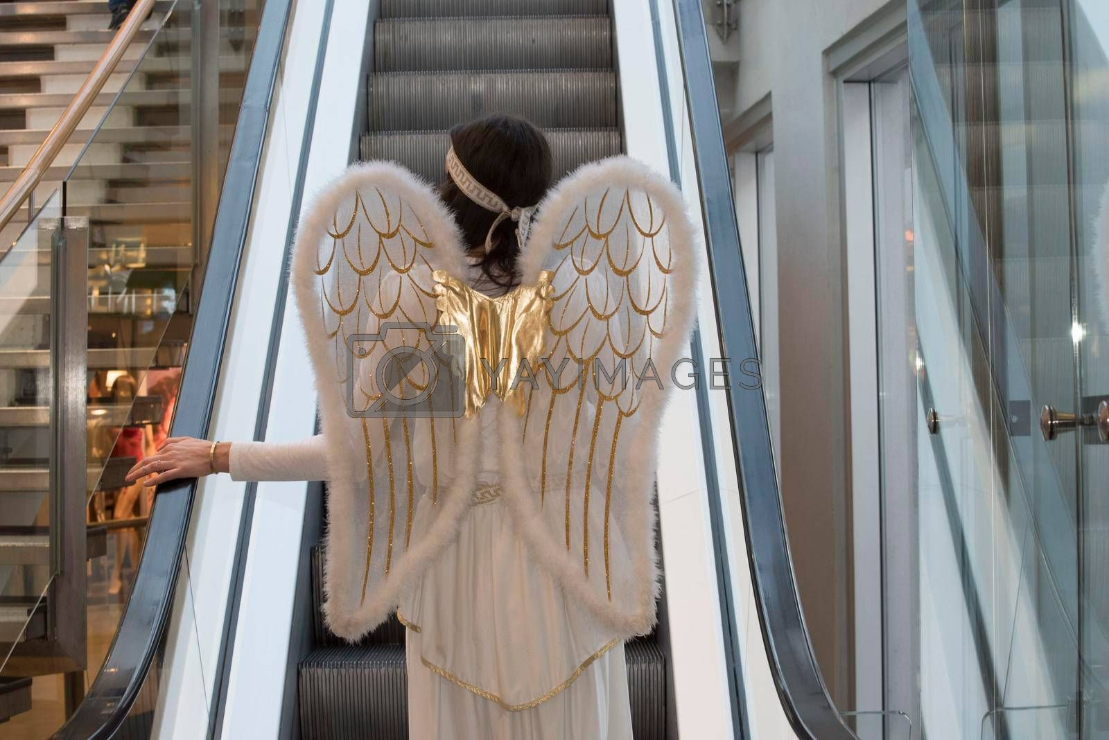 Woman in angel costume on escalator at Christmas time in a shopping center