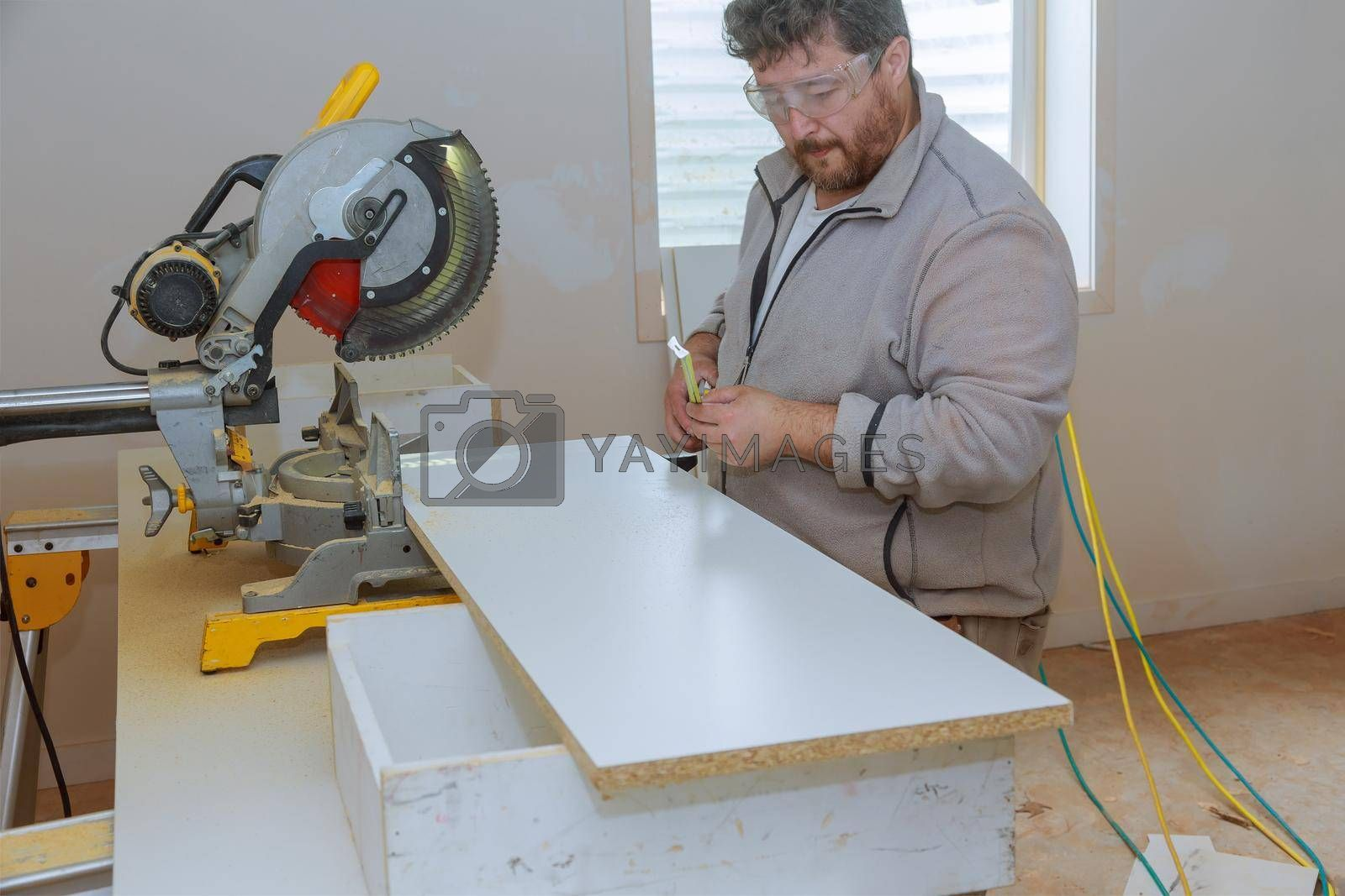Building contractor worker using measuring and marking a board before cutting wooden shelf for a new building