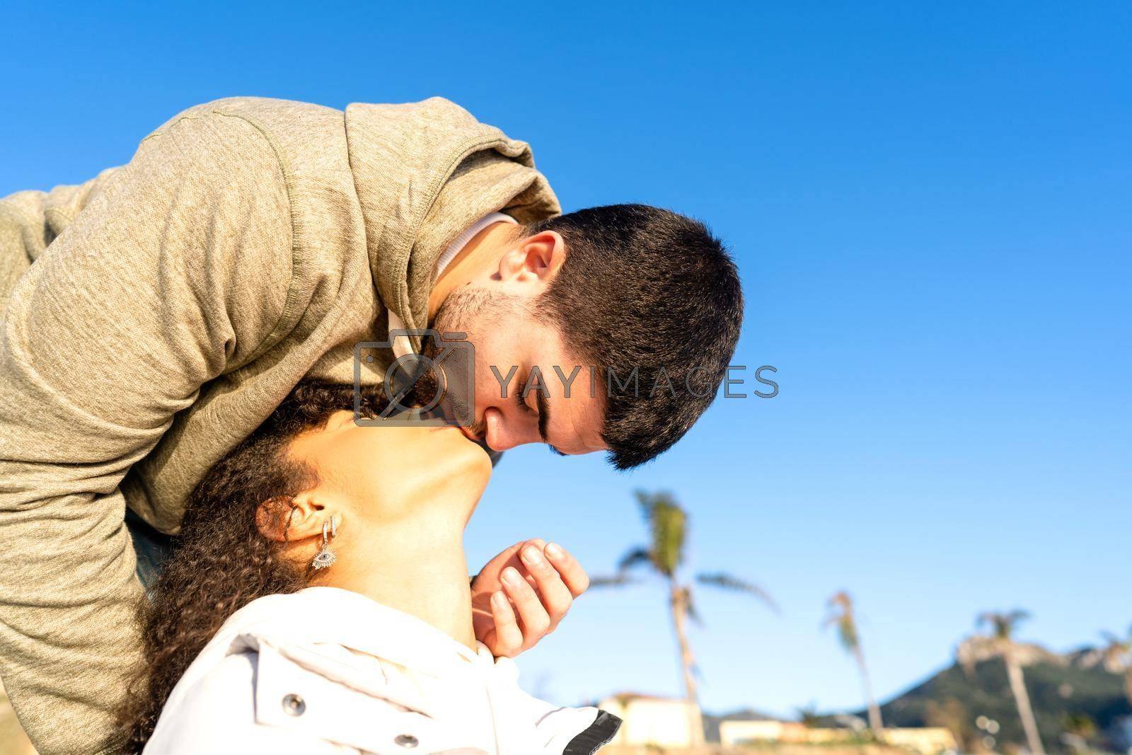 Royalty free image of Handsome guy kissing her african-american black girlfriend approaching her mouth from above. Mixed race young couple in love romance vacation scene in sea or ocean resort with copy space in blue sky by robbyfontanesi