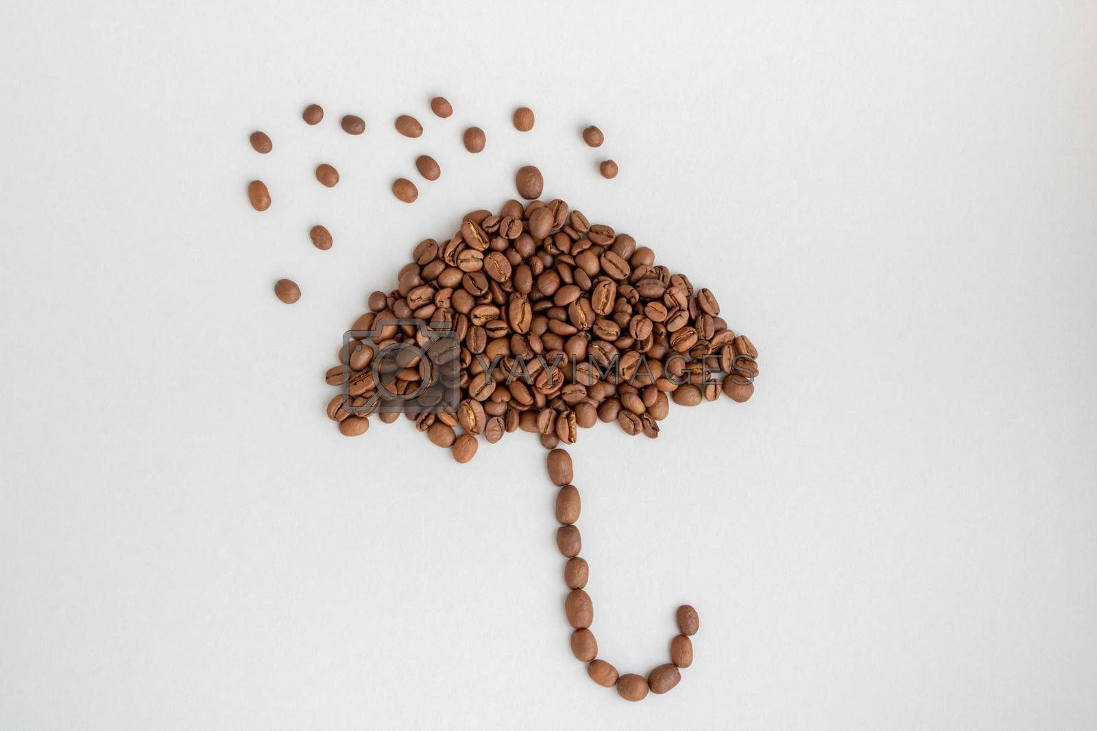 Coffee beans in the shape of an umbrella on a gray background.