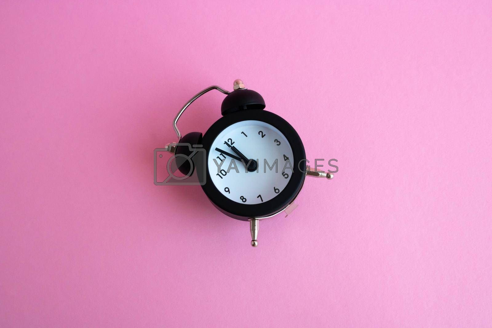 Black vintage alarm clock lying on a pink background.