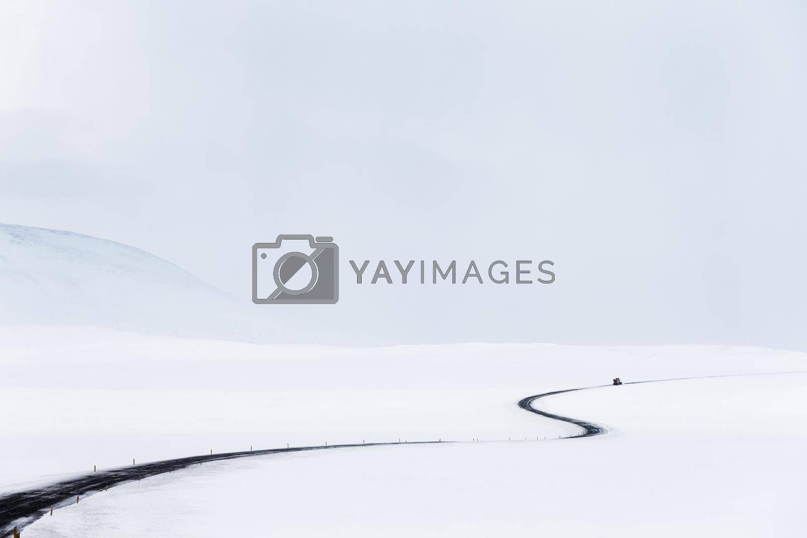 Amazing Winter Landscape. Empty Road among Fields covered with Snow. Natural Grey White Background. Stormy Weather of Iceland.