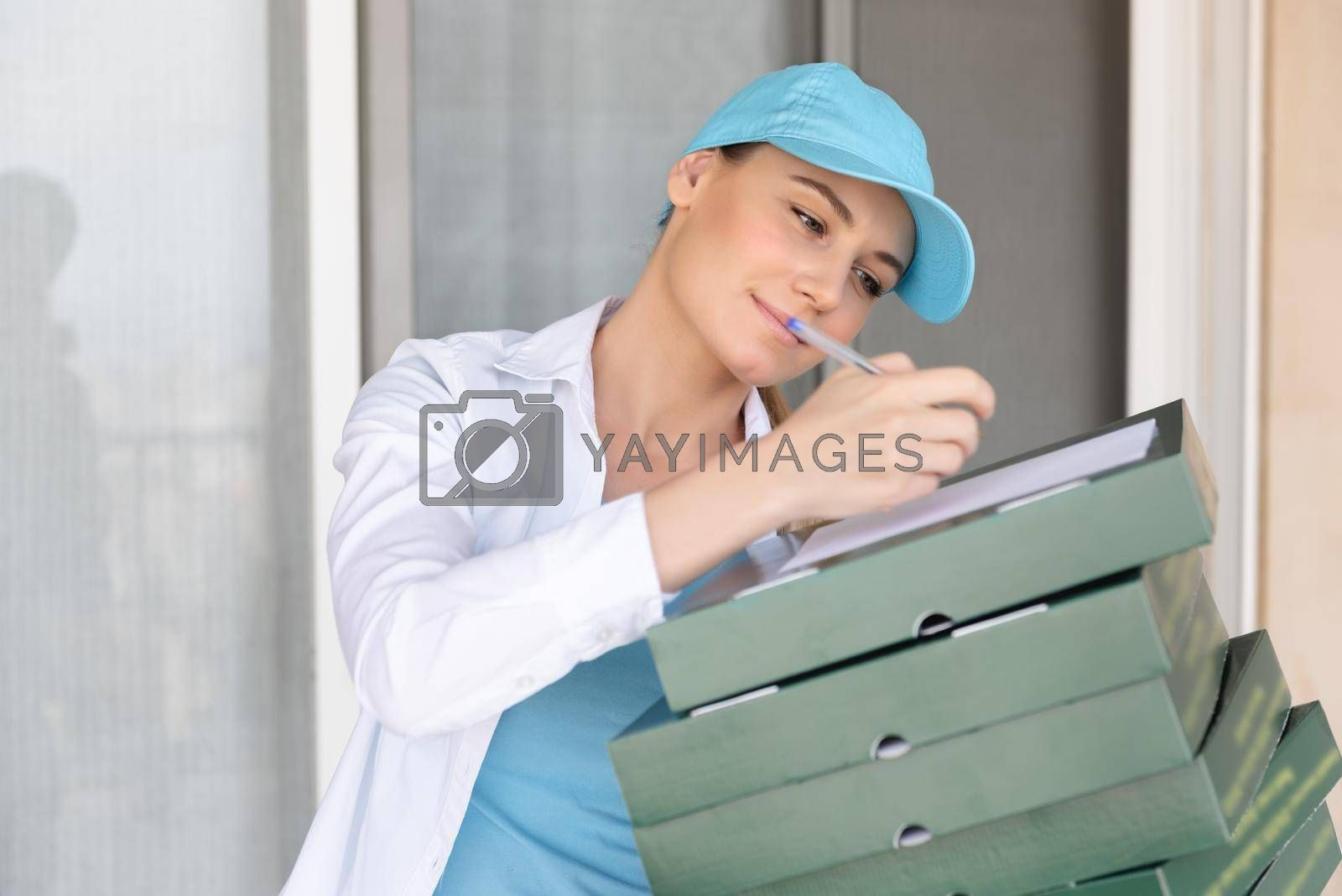 Nice Delivery Girl Wearing Special Uniform Signs a Check for Payment. Delivering Necessary Products. Modern Online Business. Conceptual Photo of a Service Occupation.