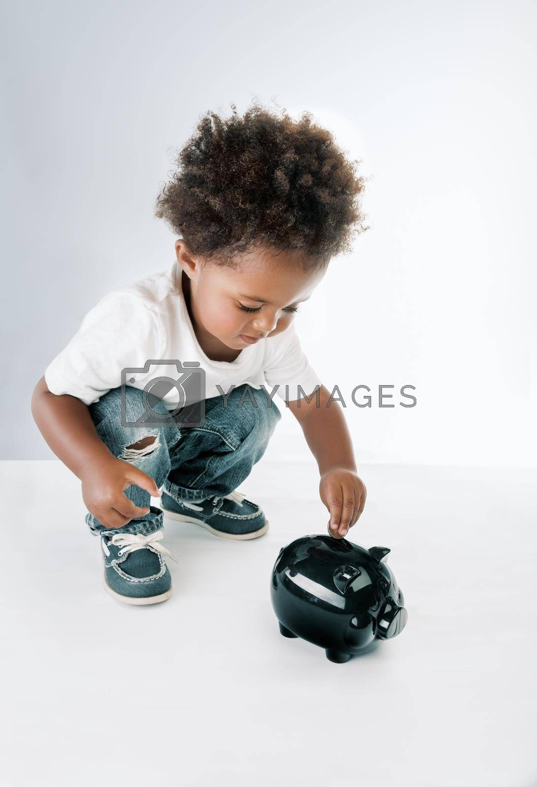 Portrait of a Nice African American Child Putting Coins in to the Pig-shaped Money Box. Isolated on Grey White Background. Hope for Better Future