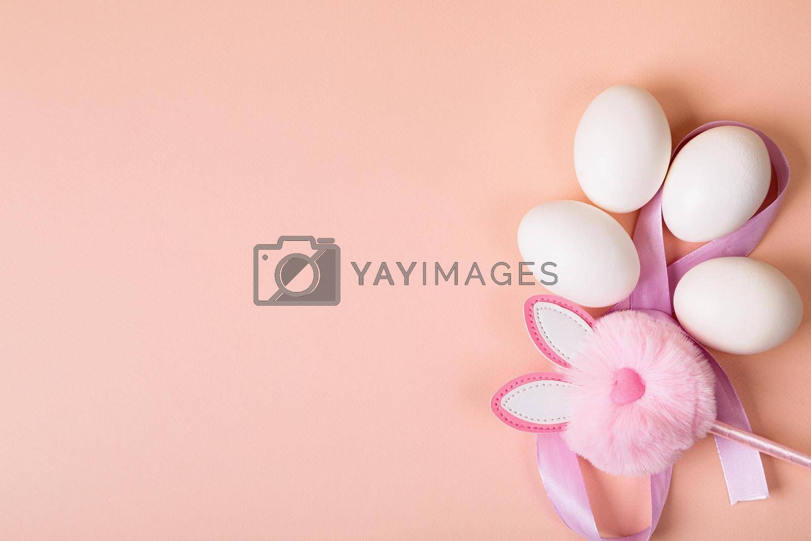 Easter. White eggs with an artificial rabbit on a uniform pink background. Place for text.