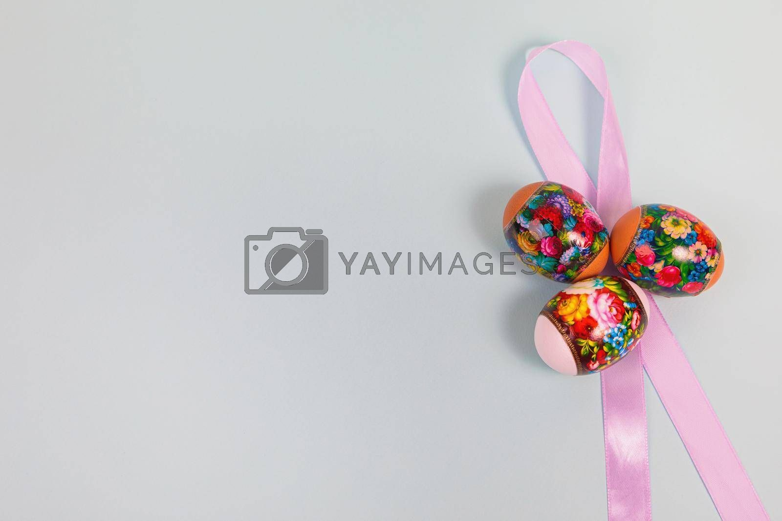 Easter. Khokhloma eggs on a uniform blue background with a ribbon. Place for text.