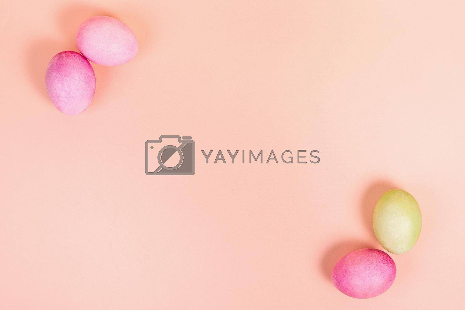 Easter. Multi-colored eggs on a uniform pink background with place for text. View from above