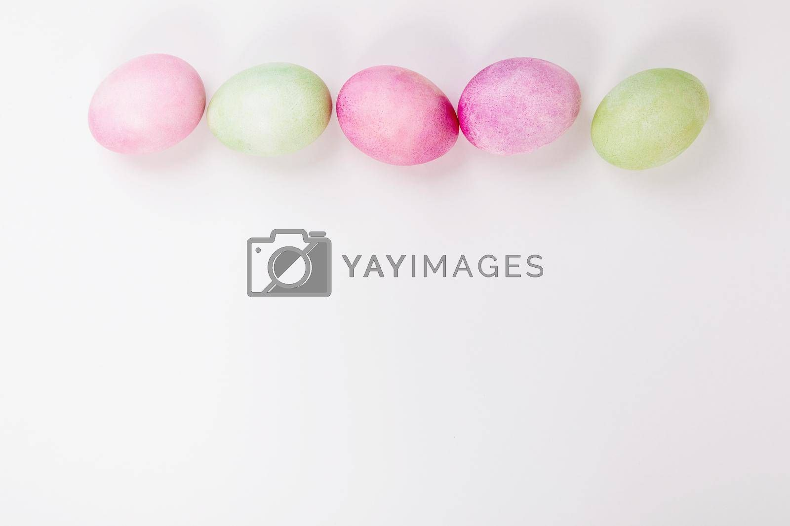 Multi-colored eggs with twigs, on a white background with a place for text. by Yurich32