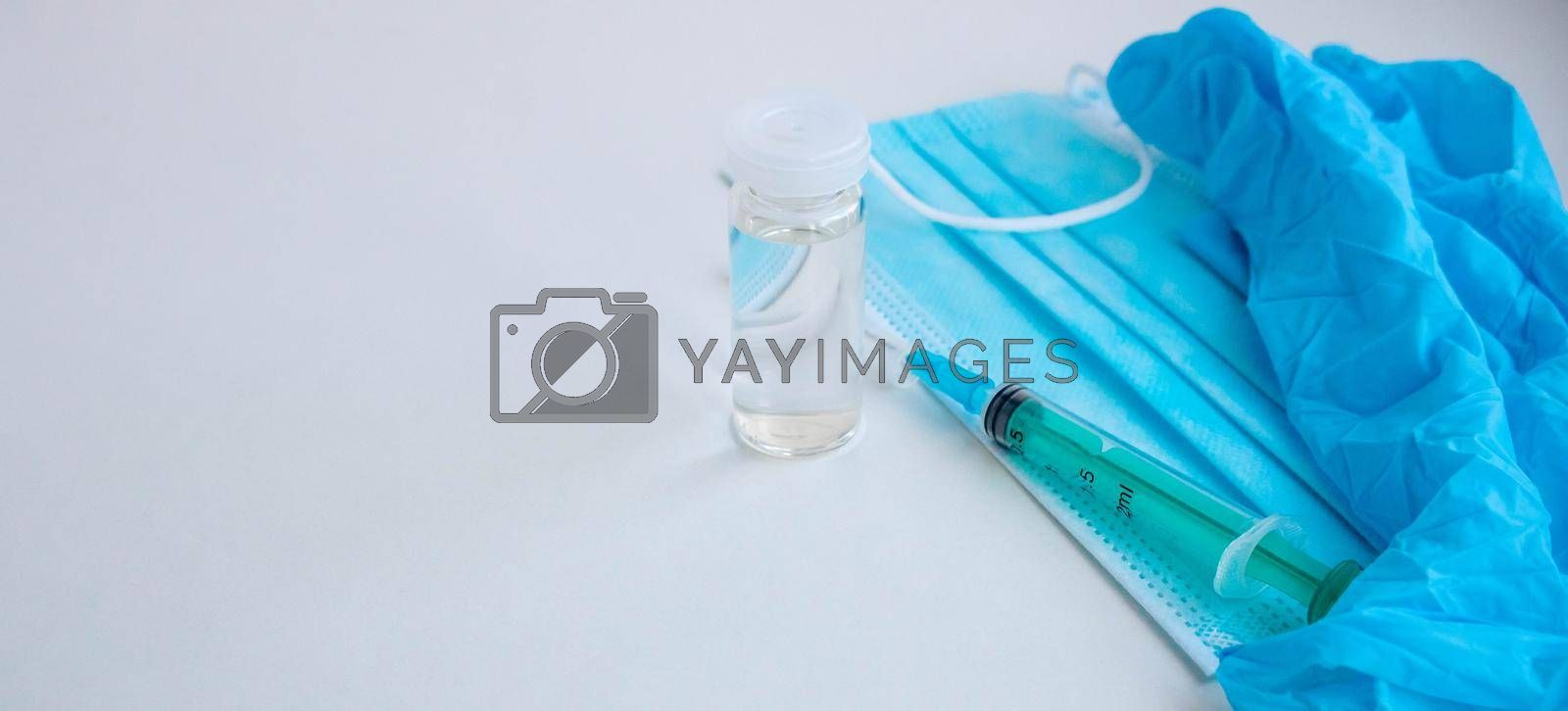 A syringe, gloves, mask, and a bottle of vaccine stand on a blue background. For the prevention, immunization and treatment of coronavirus infection. The concept of medicine and health care.