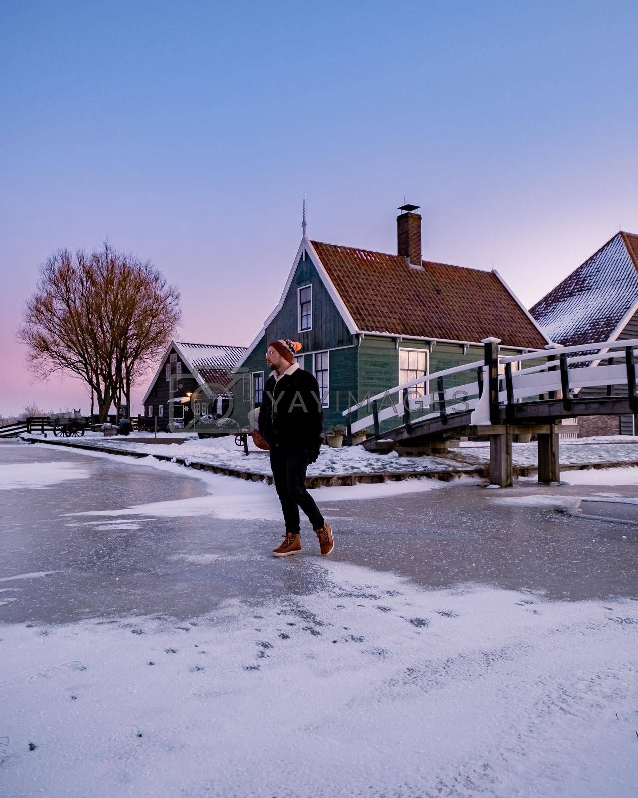 young man walked in the snow, snow covered windmill village in the Zaanse Schans Netherlands, historical wooden windmills in winter Zaanse Schans Holland during winter