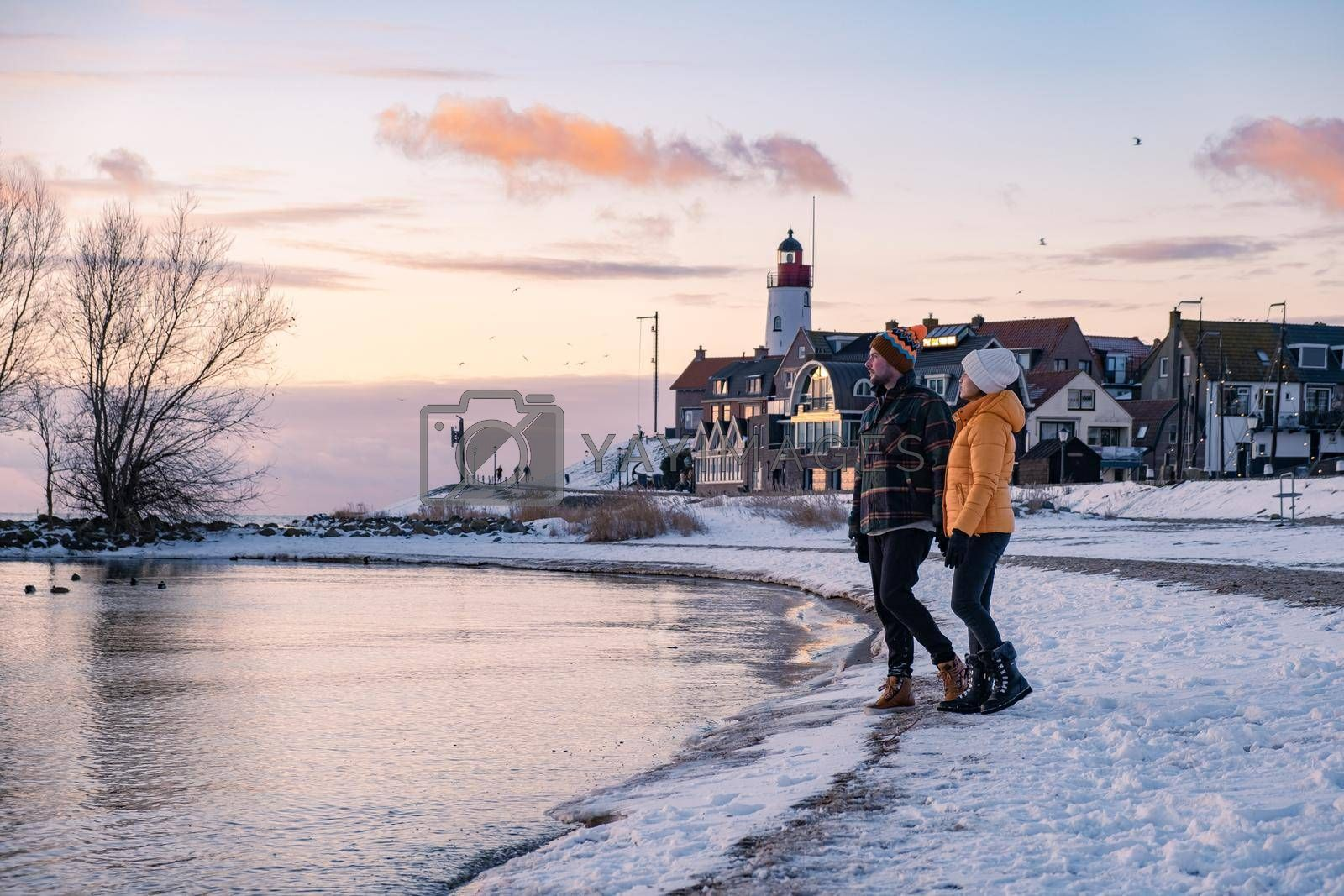 couple men and woman by the lighthouse of Urk Netherlands during winter in the snow. Winter weather in the Netherlands by Urk