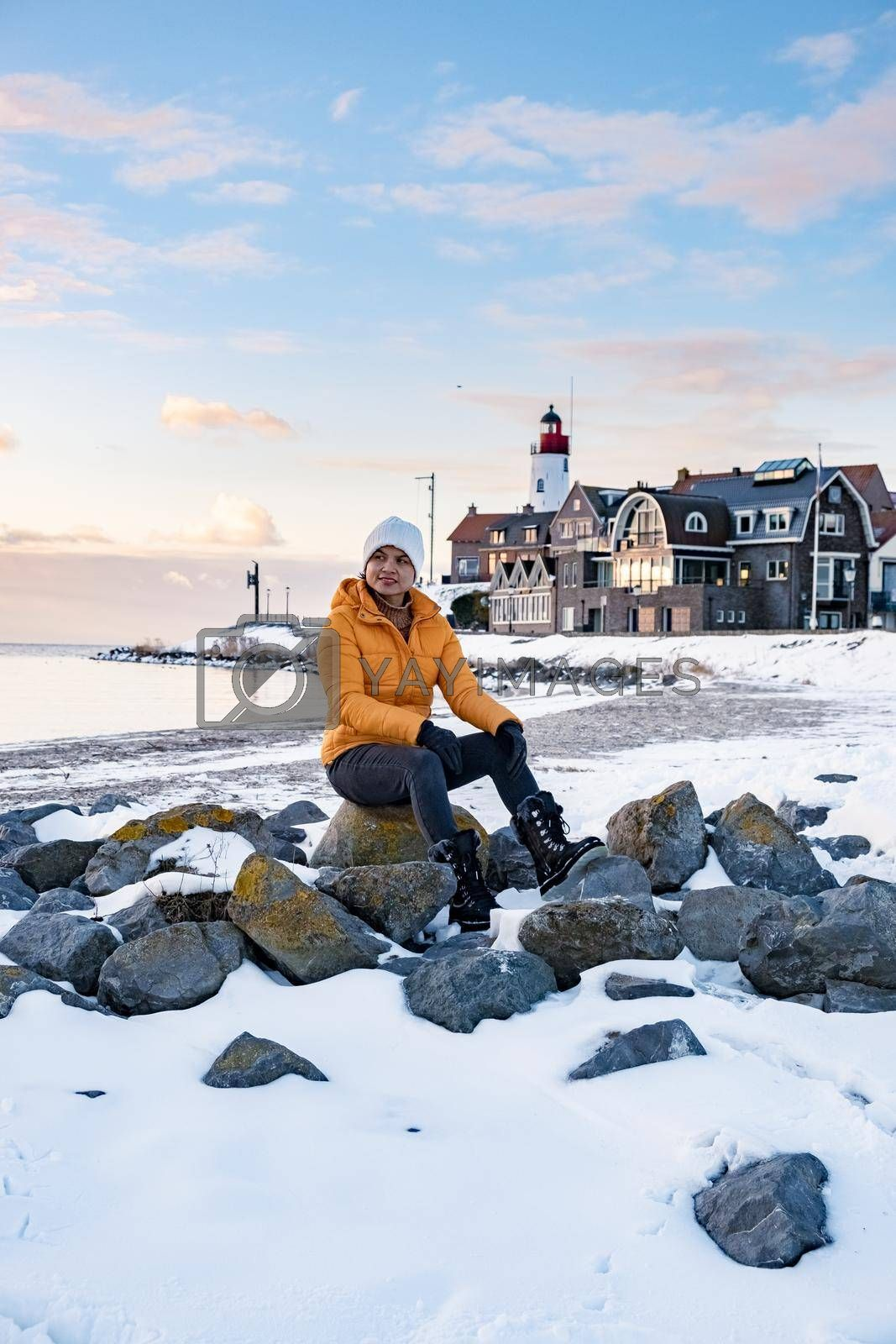 woman by the lighthouse of Urk Netherlands during winter in the snow. Winter weather in the Netherlands by Urk