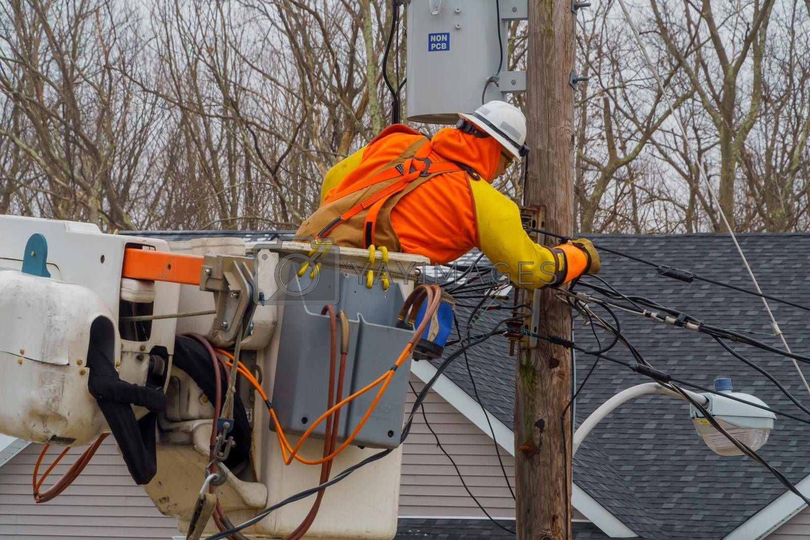 10 FEBRUARY NYC NY USA: Electrician repair system of electric wire on wooden pylon after snowfall wet snow to electric wires.