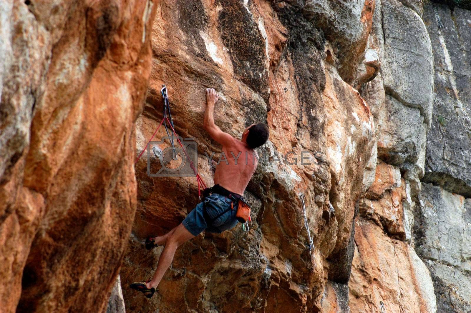 man with safety rope doing sport climbing at a mountain wall