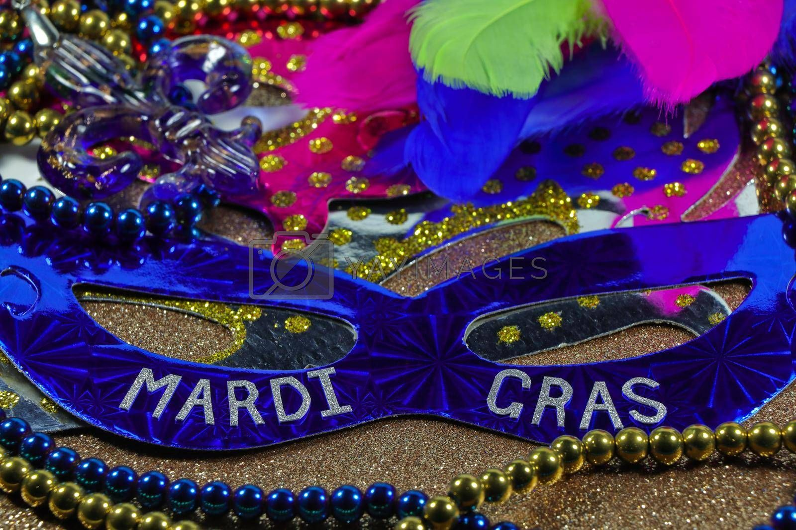 Mardi Gras carnival theme party masks with feathers and jewelry on textured gold surface abstract