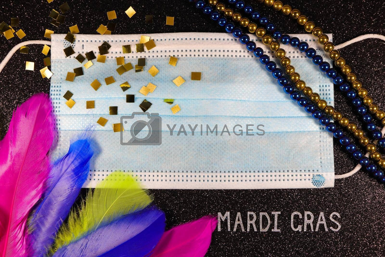 Mardi Gras carnival theme medical facemask with feathers and bead strings layout on textured black
