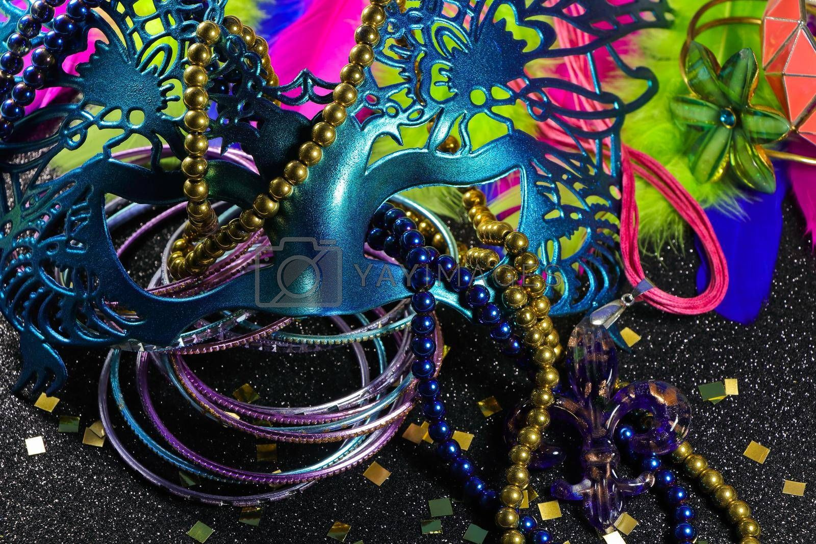 Mardi Gras carnival theme parade mask with jewelry and feathers on textured black