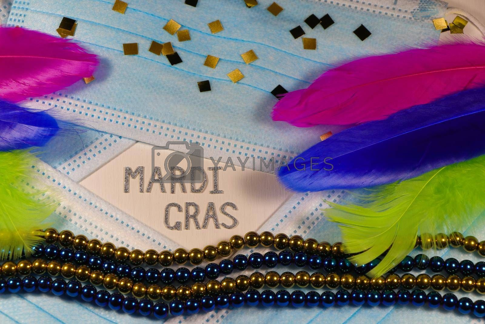 Mardi Gras carnival theme medical facemasks with bead strings and feathers layout on white