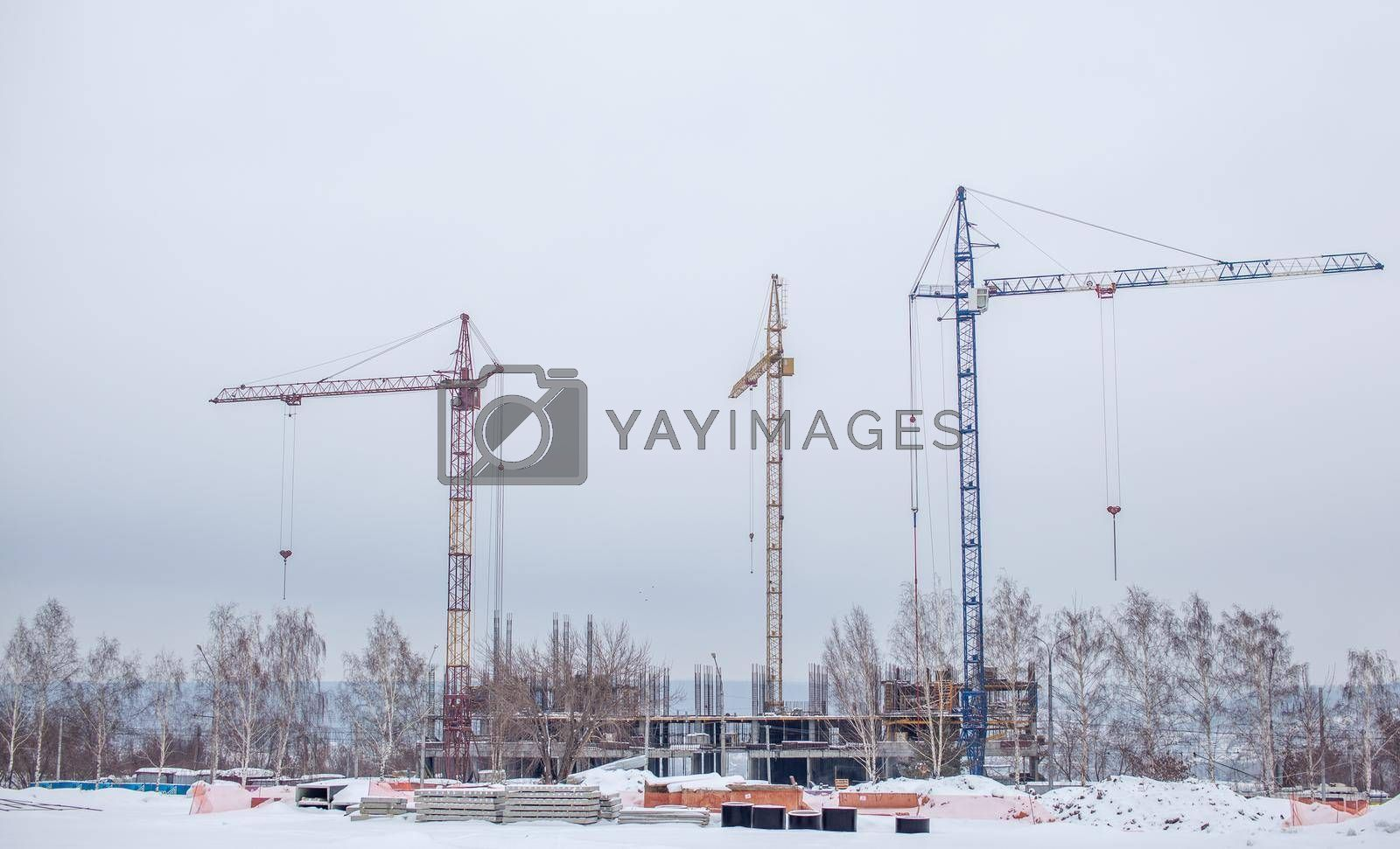 High-rise crane for construction on the sky background. Construction site with high-rise cranes. Sale of a tower crane during the economic crisis.