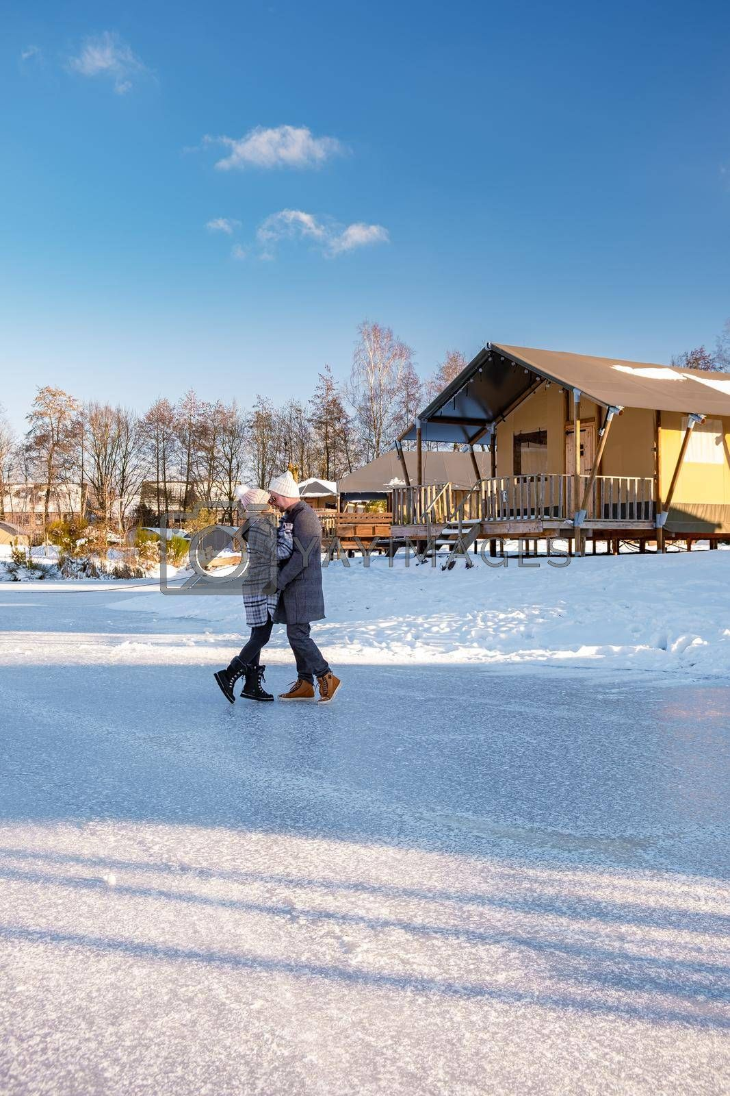 couple man and woman mid age walking in the snow with tented camp on the background, snow covered hills of the Sallandse Heuvelrug, Landscapes of the Holterberg near Holten, The Netherlands. Winter in the Netherlands