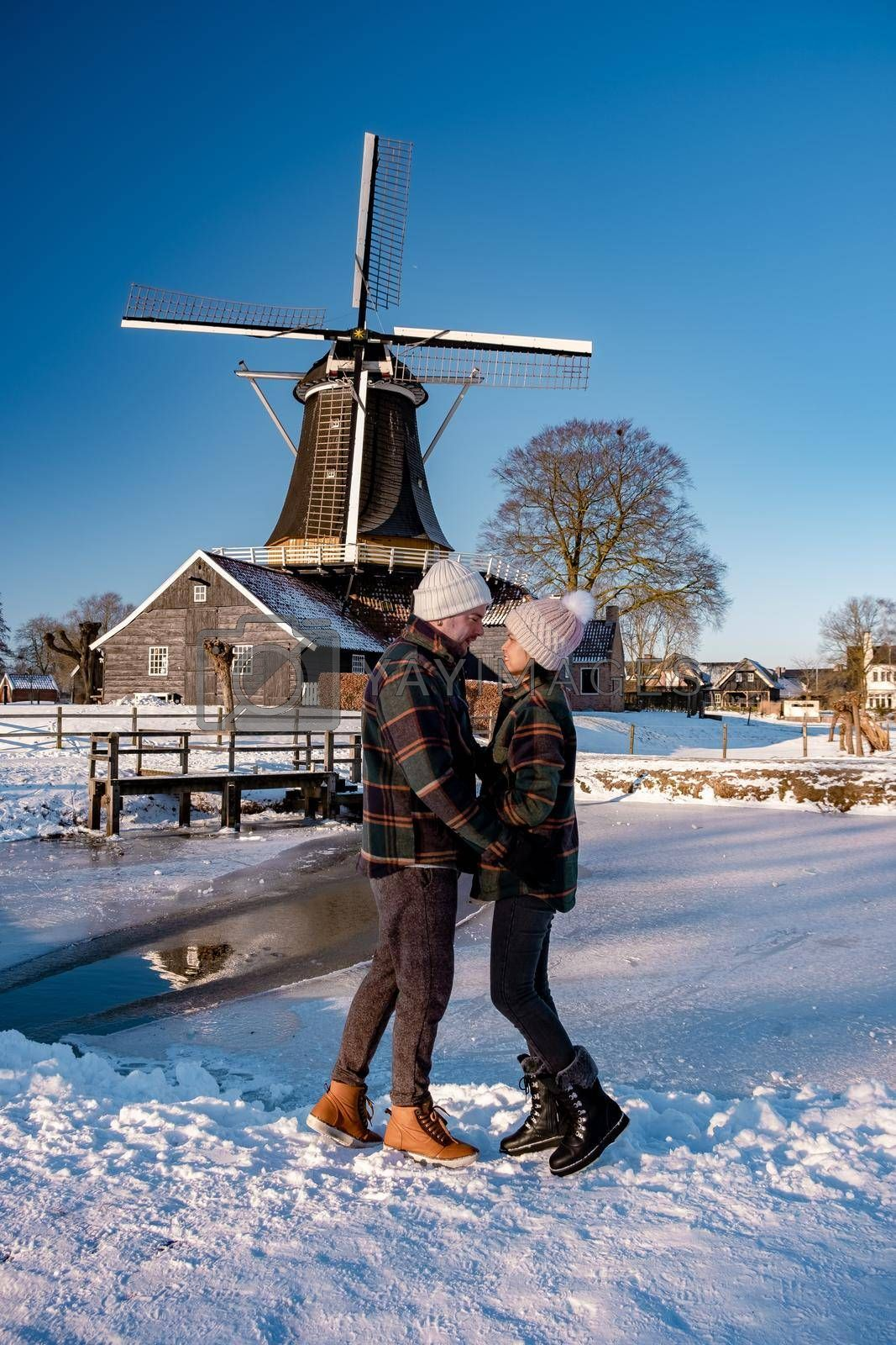 Pelmolen Ter Horst, Rijssen covered in a snowy landscape Overijssel Netherlands, historical wind mill during winter. wooden old windmill in Holland, couple men and woman walking in the snow