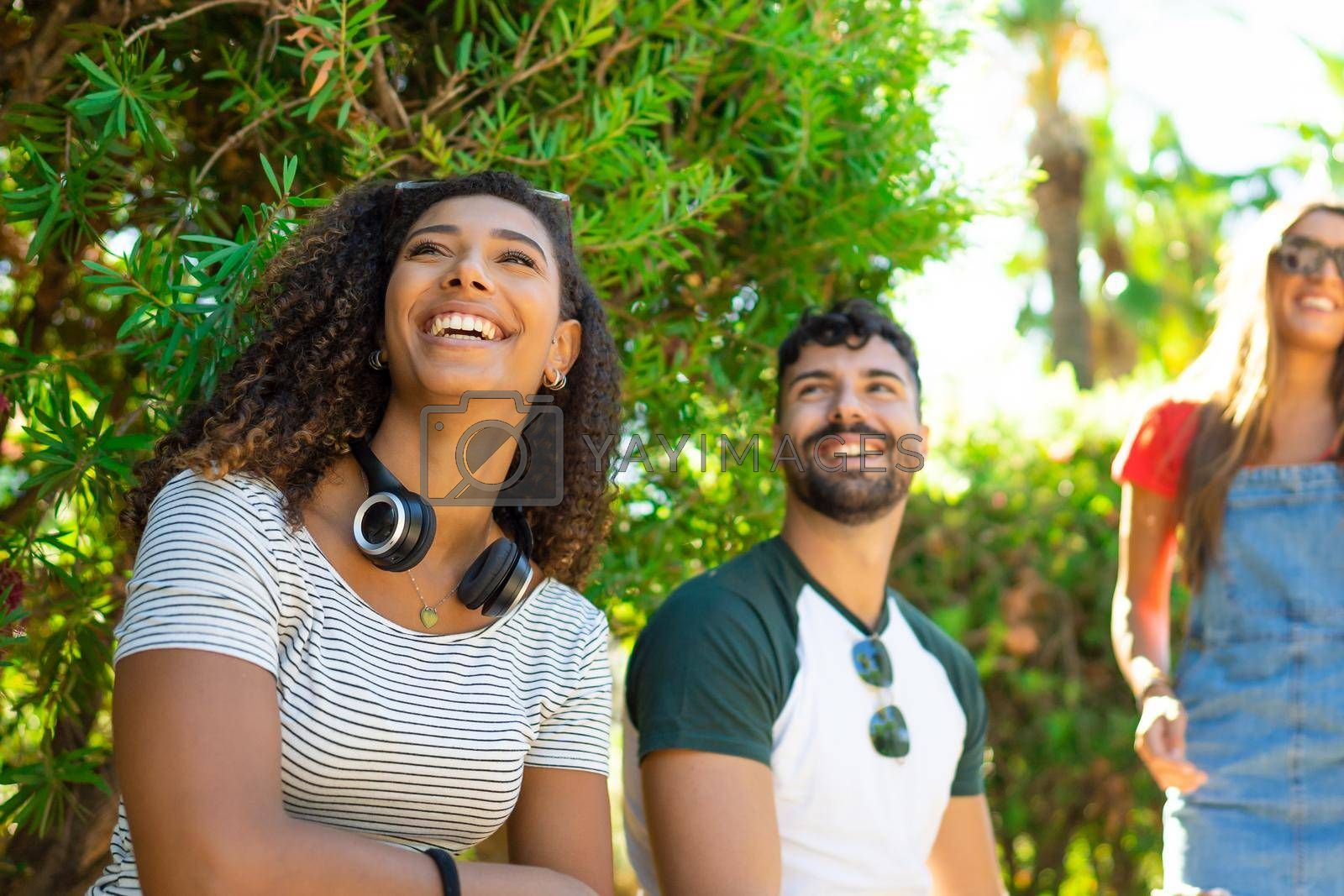 Afro american young woman with wireless headphones sitting in the city park with her millennials friends. Group of carefree hipster having fun in the summer sun and the nature in town