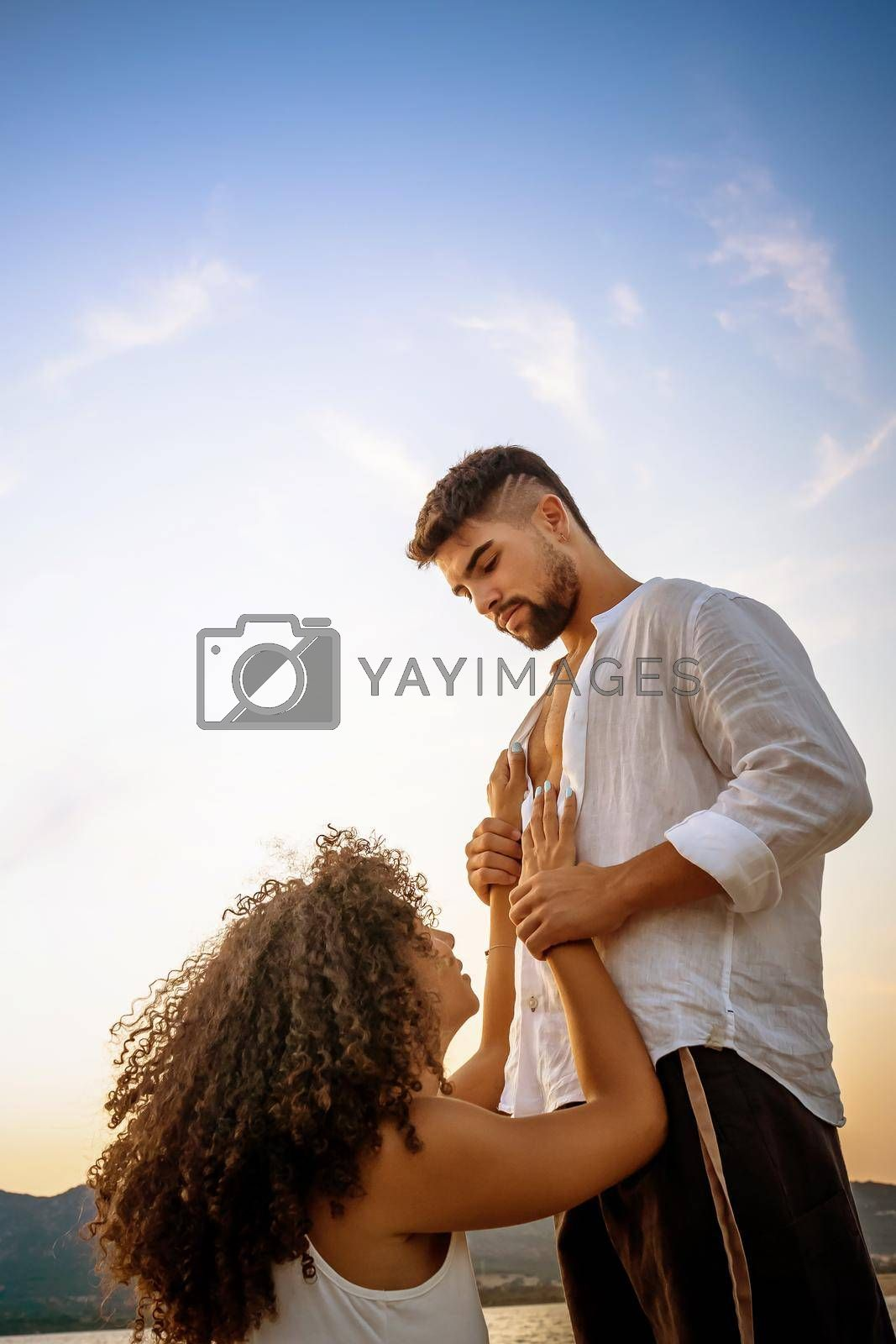 Romance scene of handsome bearded guy holding his kneeling girlfriend by the wrists looking in eyes at sunset in nature. Submissive young afro american curly woman in love in adoration of her man