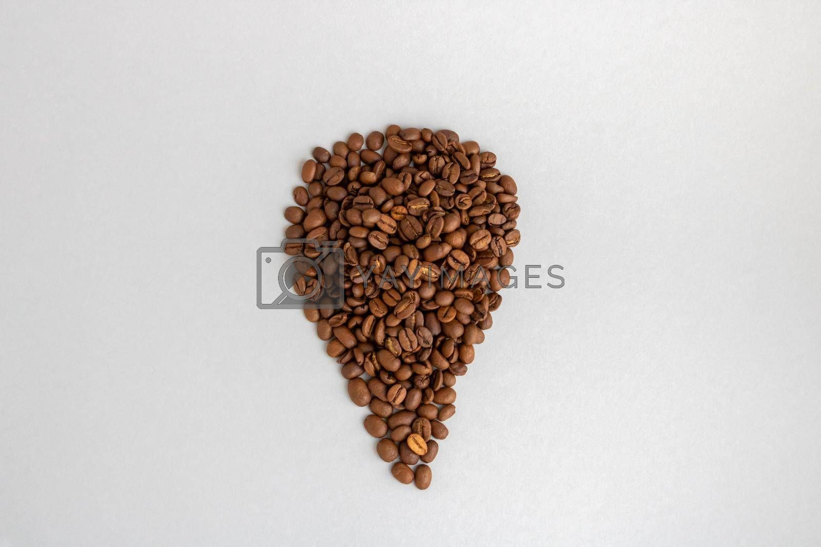 Coffee beans. Isolated on a gray background in the shape of a drop.
