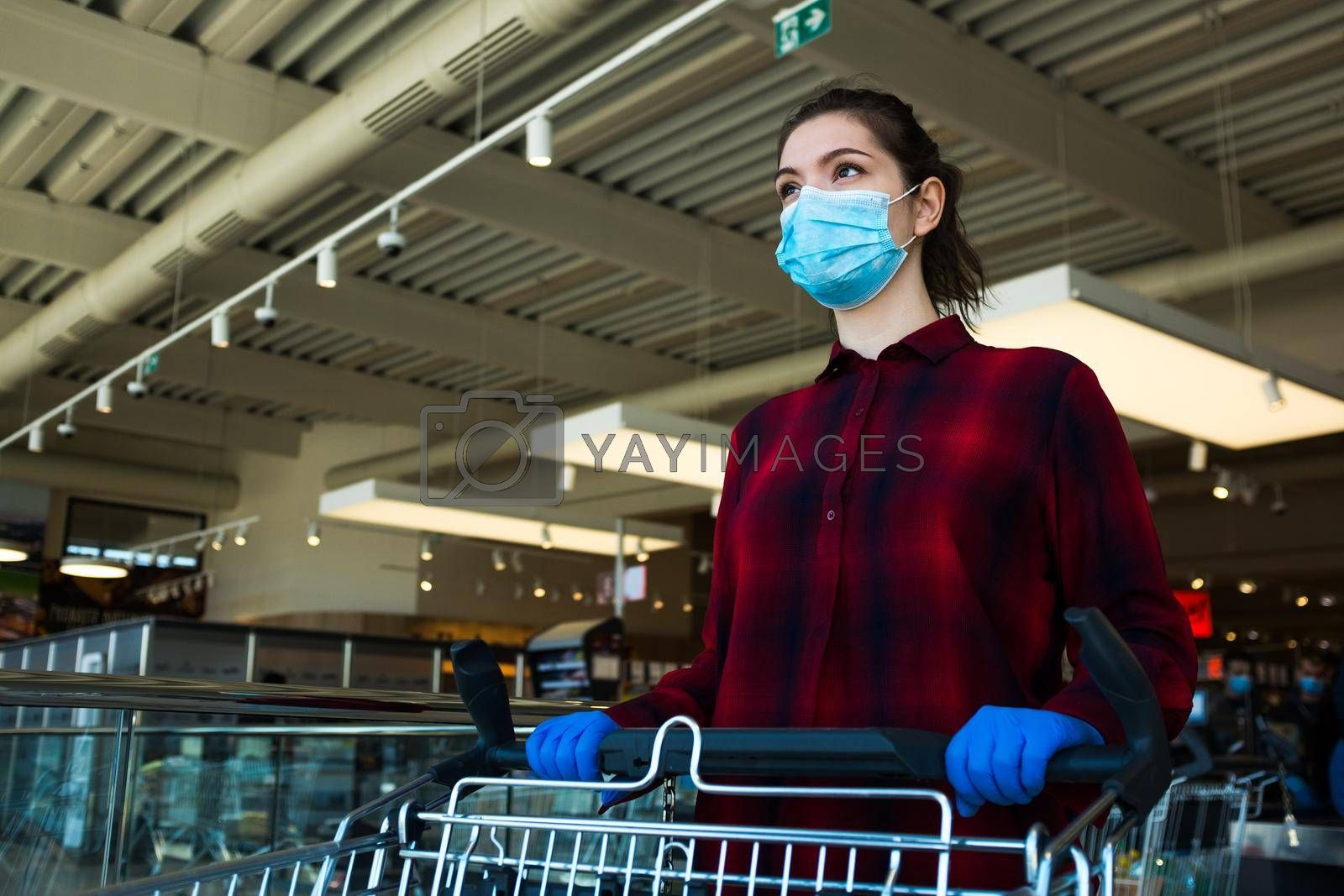 Young caucasian woman pushing shopping cart in supermarket, wearing protective blue surgical face mask and latex gloves, health and safety measurements in public due to Coronavirus COVID-19 pandemic