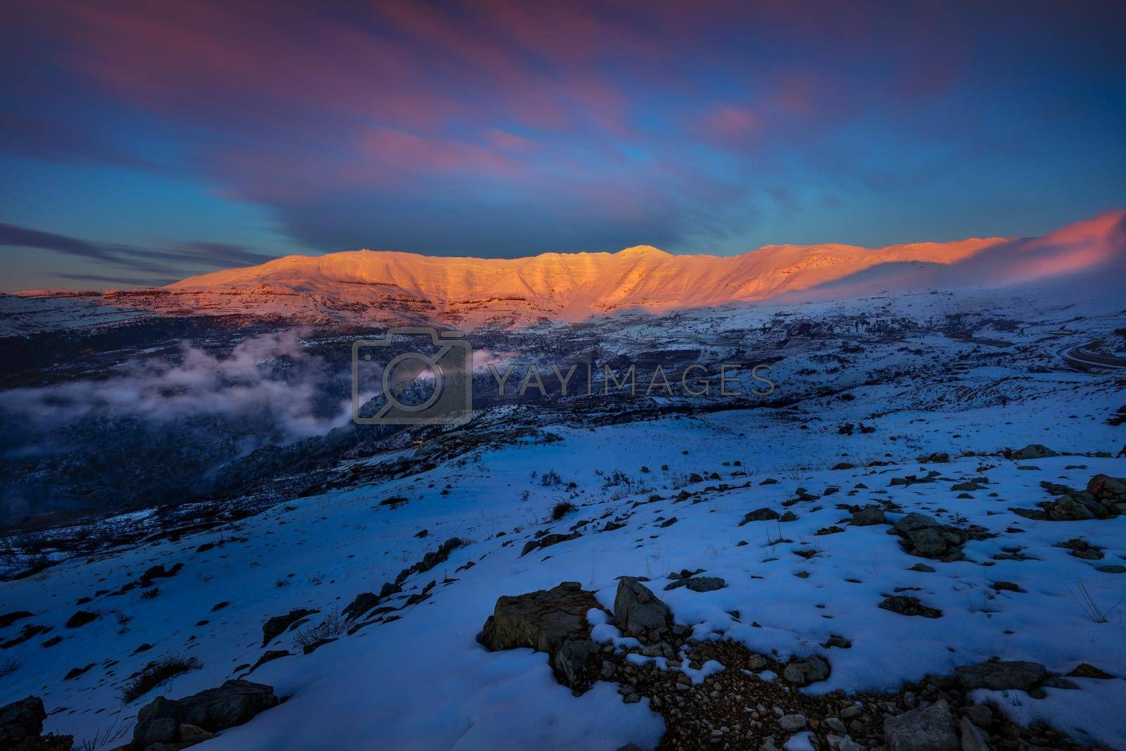Evening View on a Beautiful Mountains Covered with Snow in Bright Sunset Light. Winter Location. Tannourine. Lebanon.