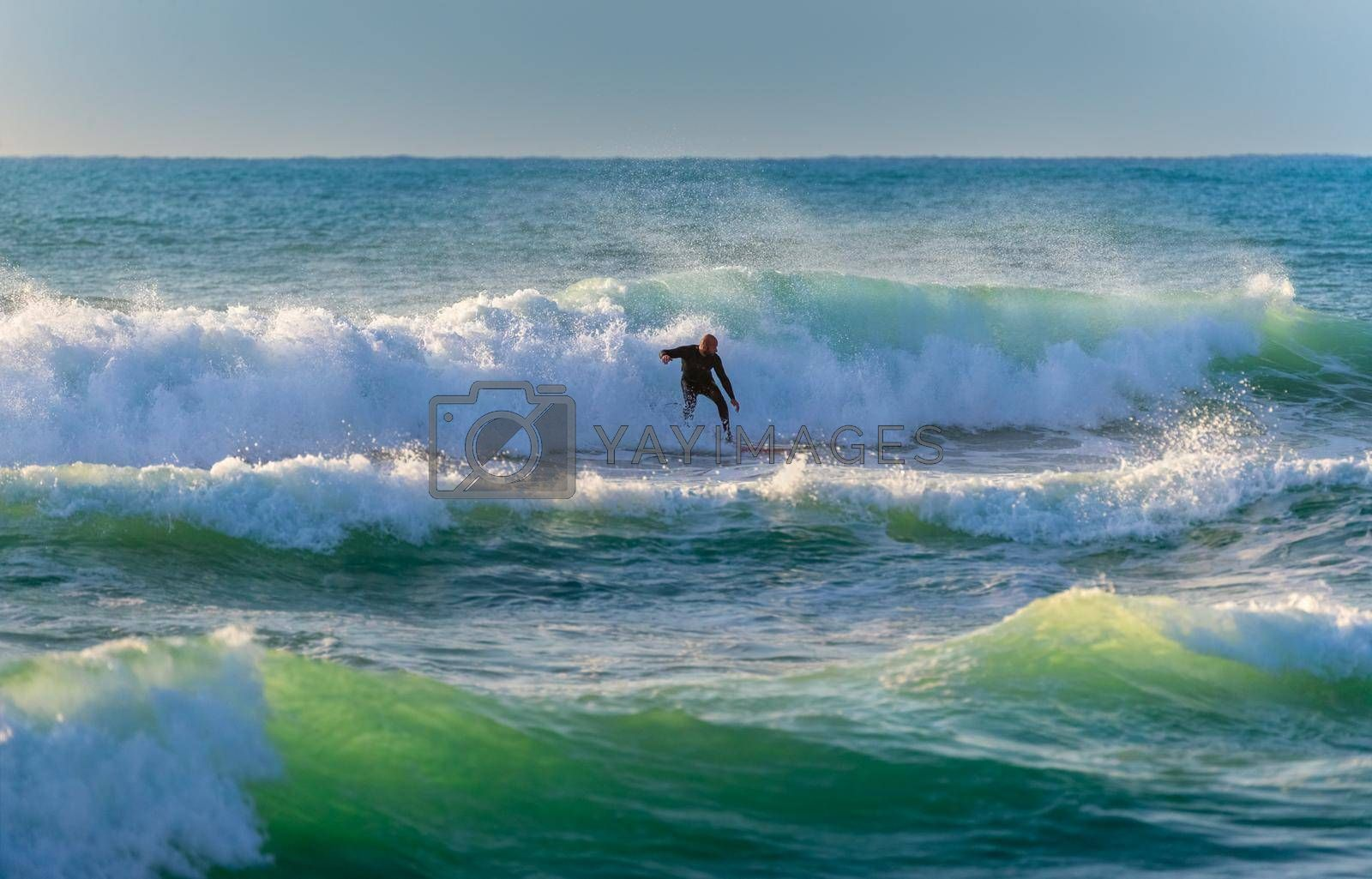 Surf. Picture of a Man Riding a Surfboard on the Crest of a Wave. Summertime Activity. Extreme Water Sport. Enjoying Summer Vacation on the Sea.