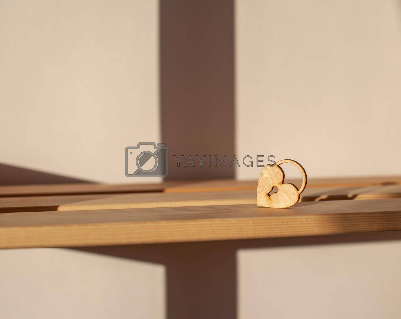 A wooden heart with a keyhole is on the shelf. The heart is illuminated by warm sunlight.