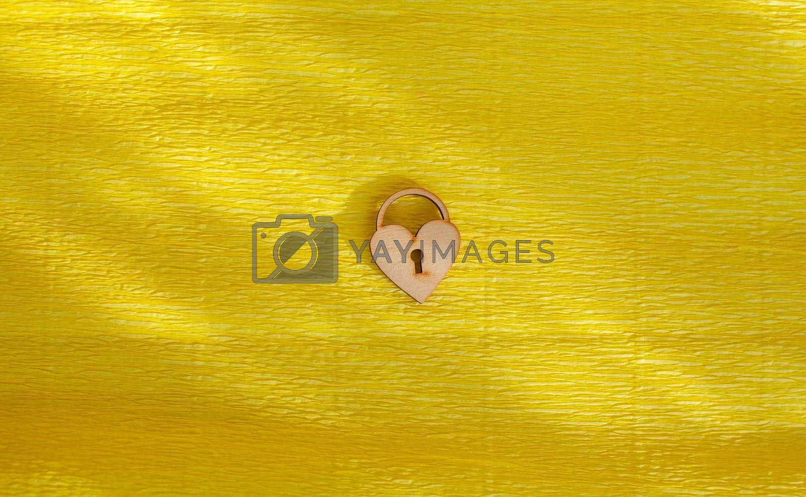 A wooden heart with a keyhole on a yellow background. by AnatoliiFoto