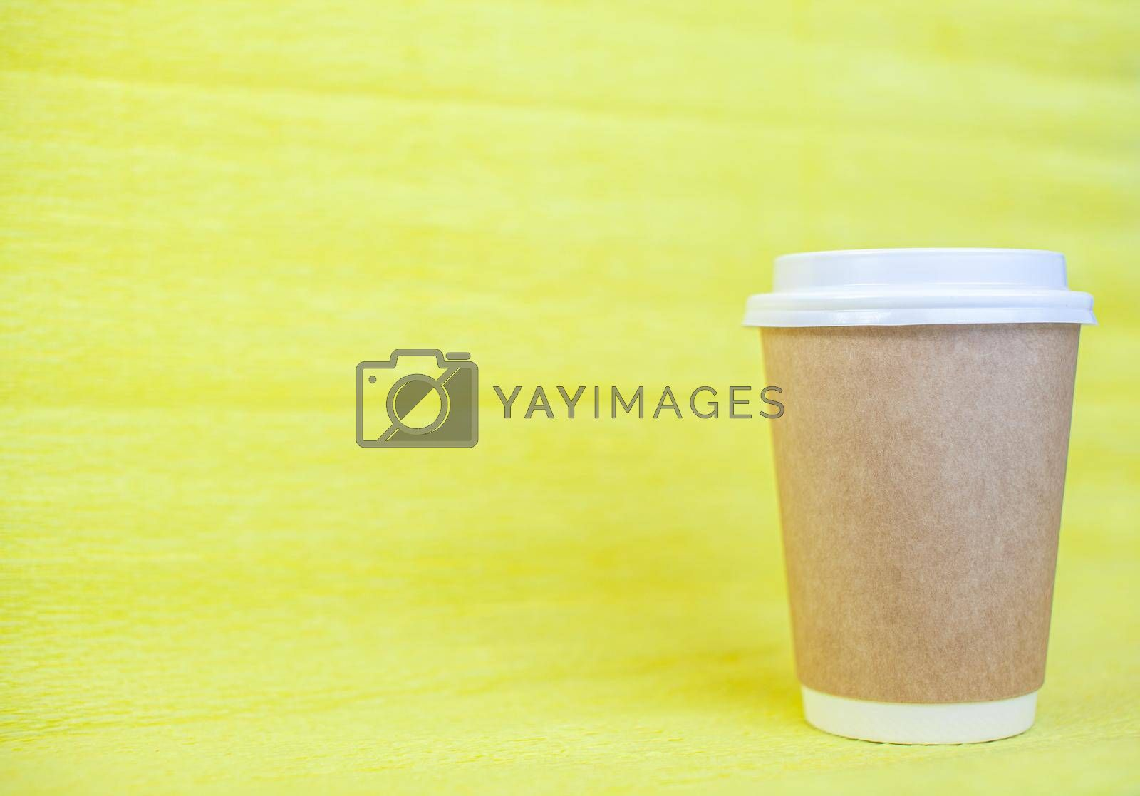 Royalty free image of Paper cup of coffee closed with a white lid on a yellow background.  by AnatoliiFoto
