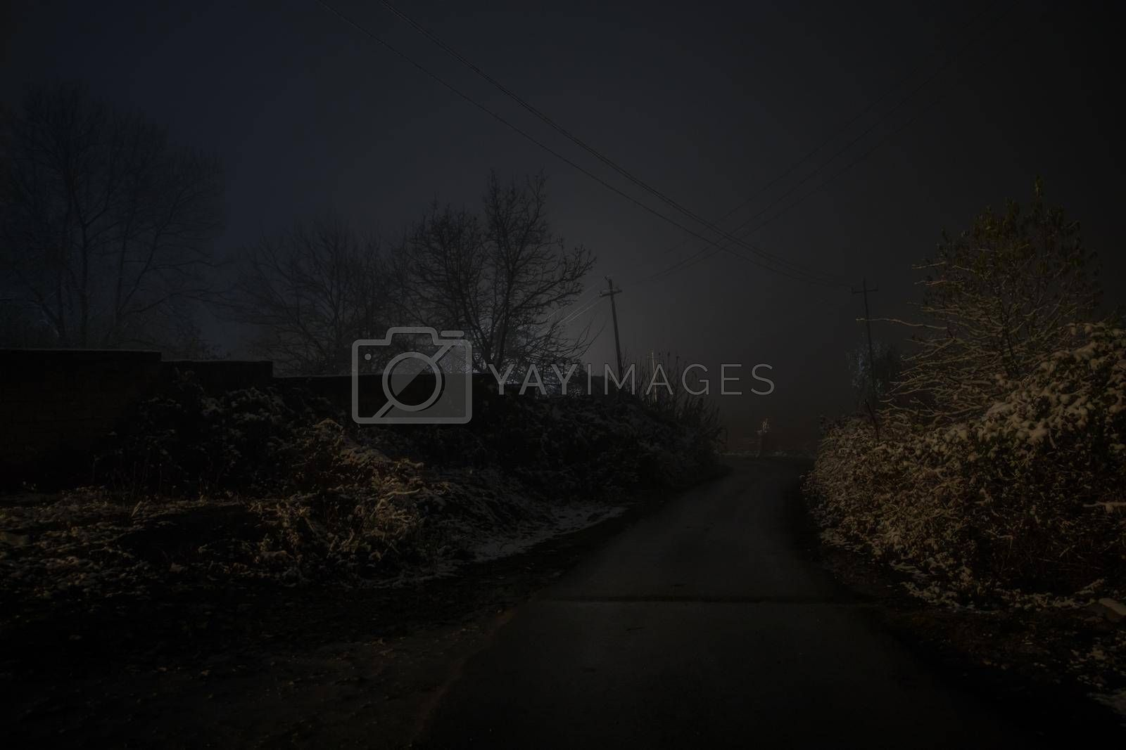 Night street country road with buildings and fences covered in fog lamp . Or Mysterious night in Azerbaijan mountain village. Long exposure shot